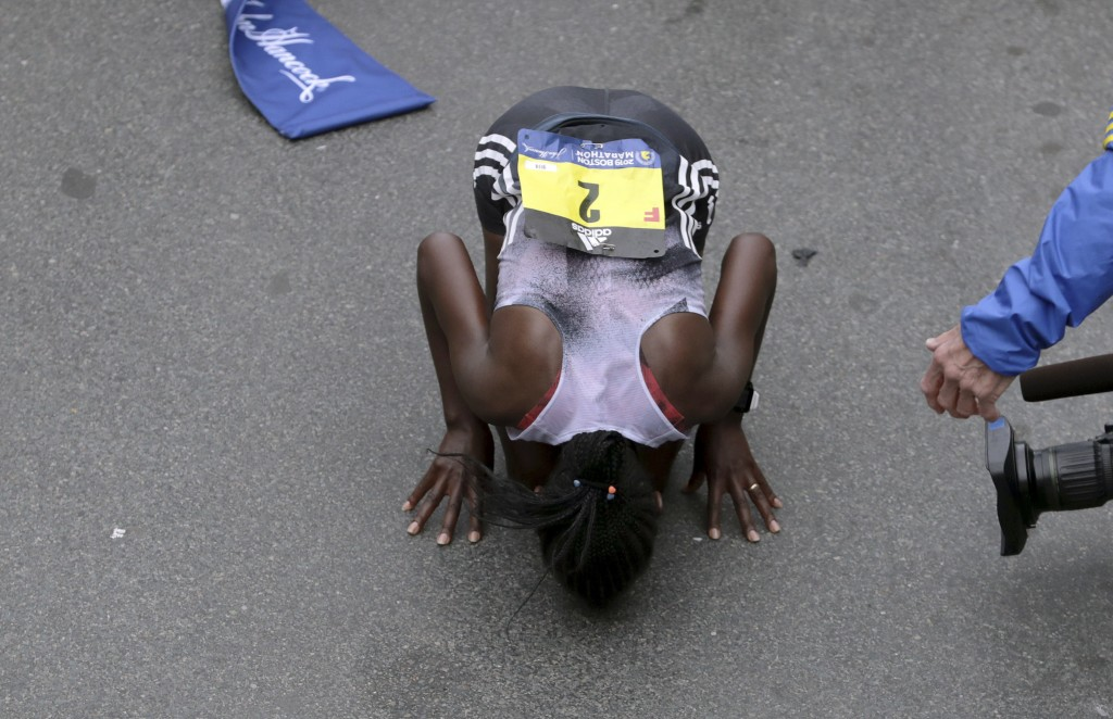 Worknesh Degefa, of Ethiopia, kisses the ground after winning the women's division of the 123rd Boston Marathon on Monday, April 15, 2019, in Boston.