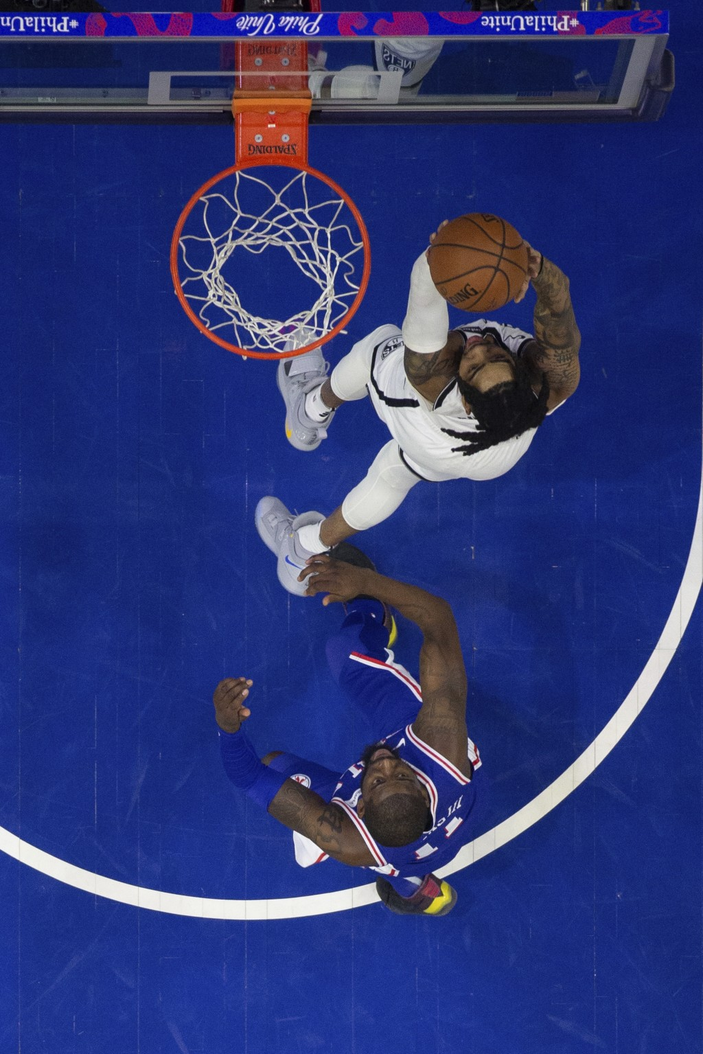 Brooklyn Nets' D'Angelo Russell, right, goes up for the shot against Philadelphia 76ers' James Ennis III, left, during the first half in Game 2 of a f...