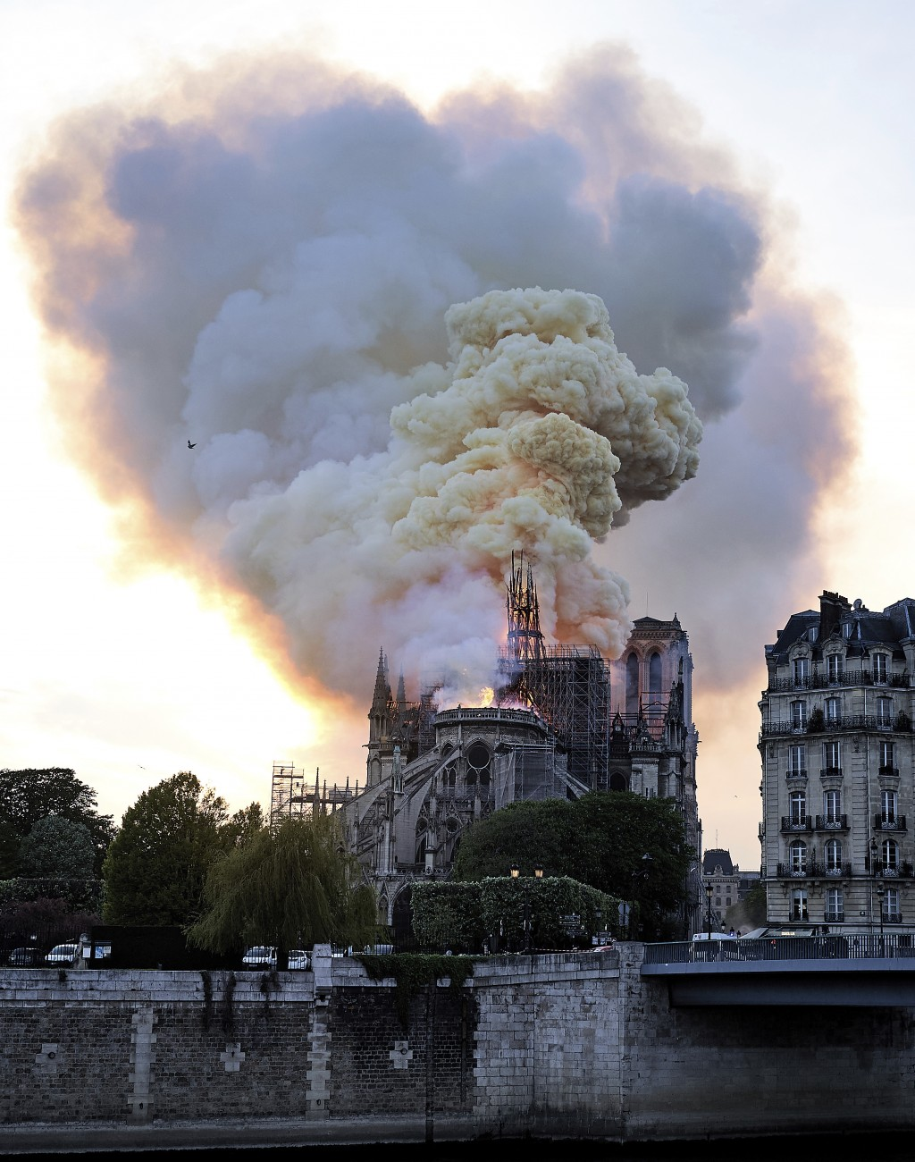 Flames and smoke rise as the spire on Notre Dame cathedral collapses in Paris, Monday, April 15, 2019. Massive plumes of yellow brown smoke is filling