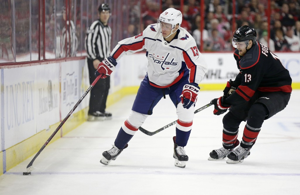 Carolina Hurricanes' Warren Foegele (13), right, and Washington Capitals' Jakub Vrana (13), of the Czech Republic, skate during the first period of Ga