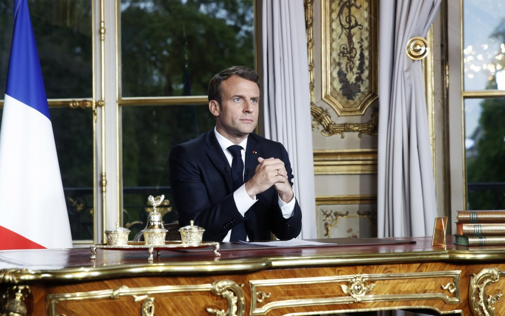 French President Emmanuel Macron sits at his desk after addressing the French nation following a massive fire at Notre Dame Cathedral, at Elysee Palac