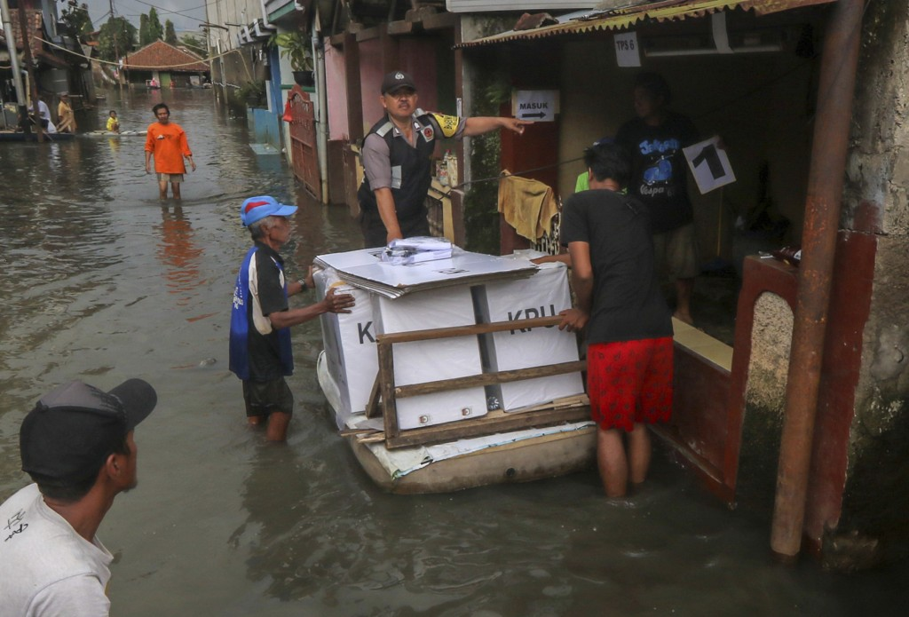 In this Tuesday, April 16, 2019, file photo, workers transport ballot boxes and other election paraphernalia through a flooded neighborhood due to hea