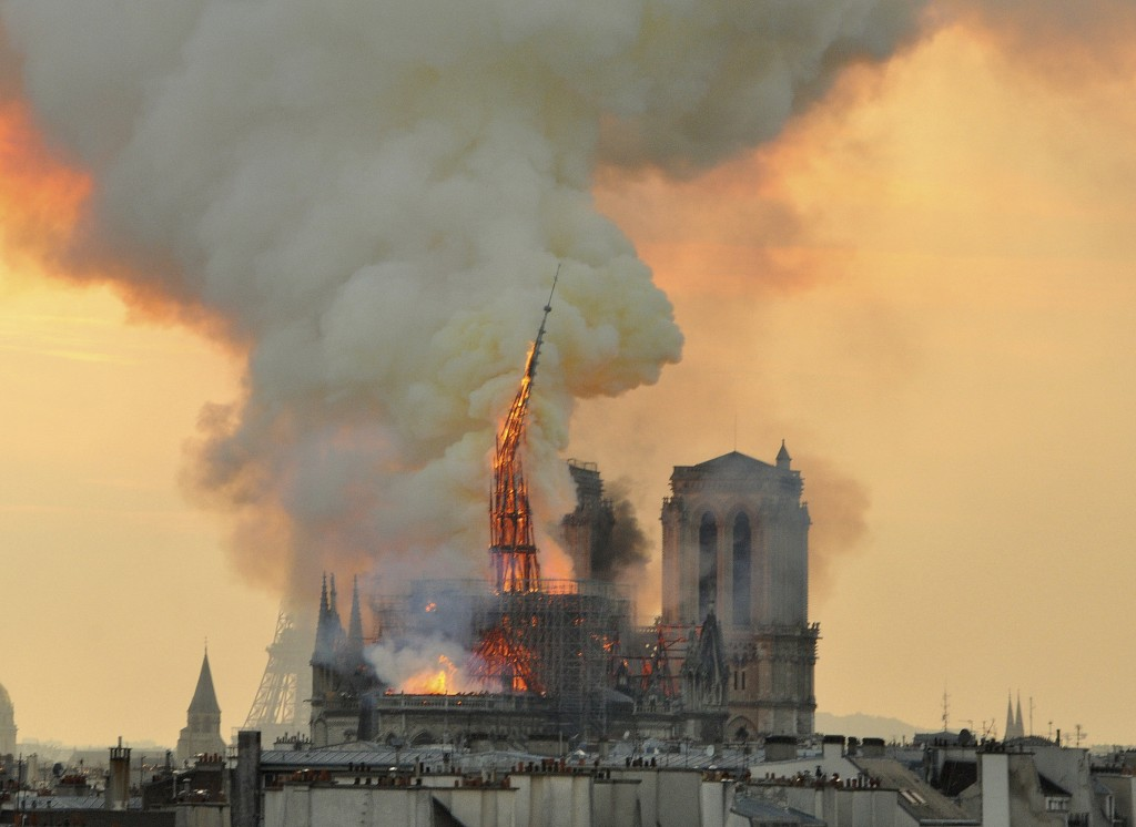 In this image made available on Tuesday April 16, 2019 flames and smoke rise from the blaze as the spire starts to topple on Notre Dame cathedral in P