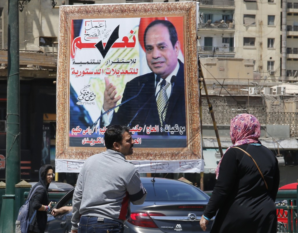 People walk past a banner supporting proposed amendments to the Egyptian constitution with a poster of Egyptian President Abdel-Fattah el-Sissi in Cai
