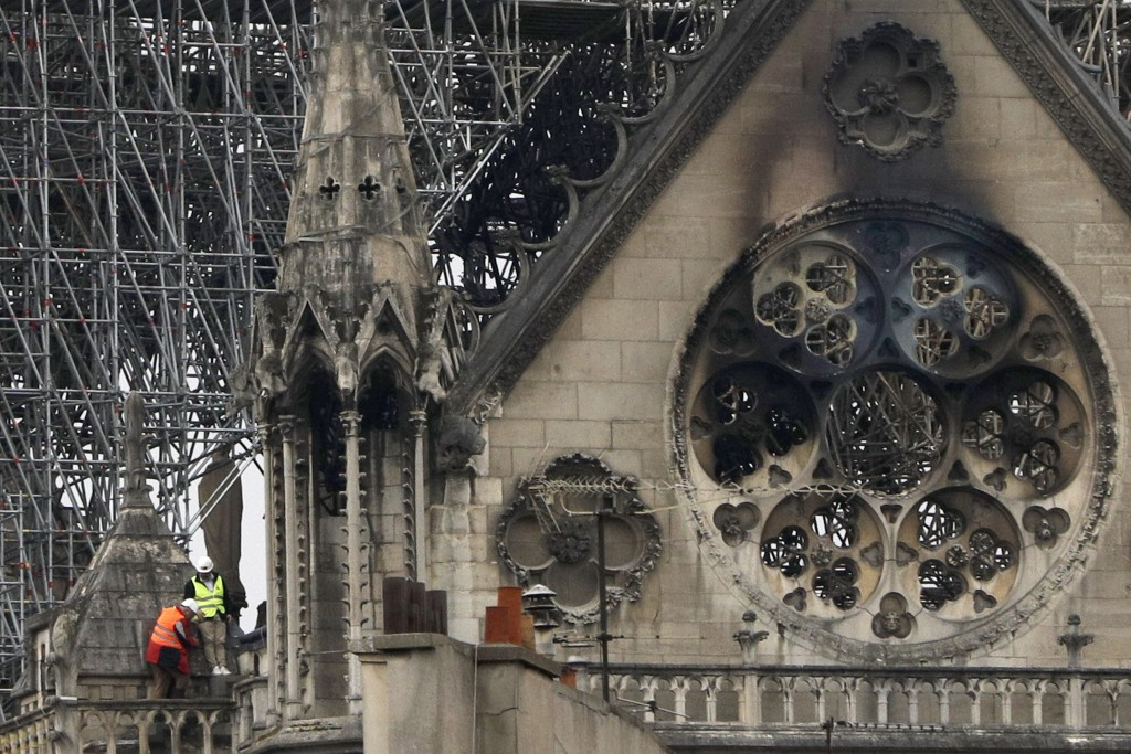 Experts inspect the damaged Notre Dame cathedral after the fire in Paris, Tuesday, April 16, 2019. Experts are assessing the blackened shell of Paris'...