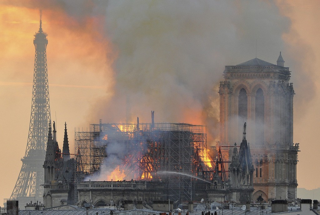 In this image made available on Tuesday April 16, 2019 flames and smoke rise from the blaze after the spire toppled over on Notre Dame cathedral in Pa...