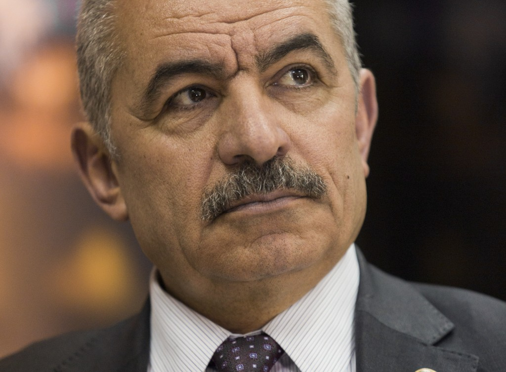 Palestinian Prime Minister Mohammad Shtayyeh listens during an interview with The Associated Press, at his office in the West Bank city of Ramallah, T