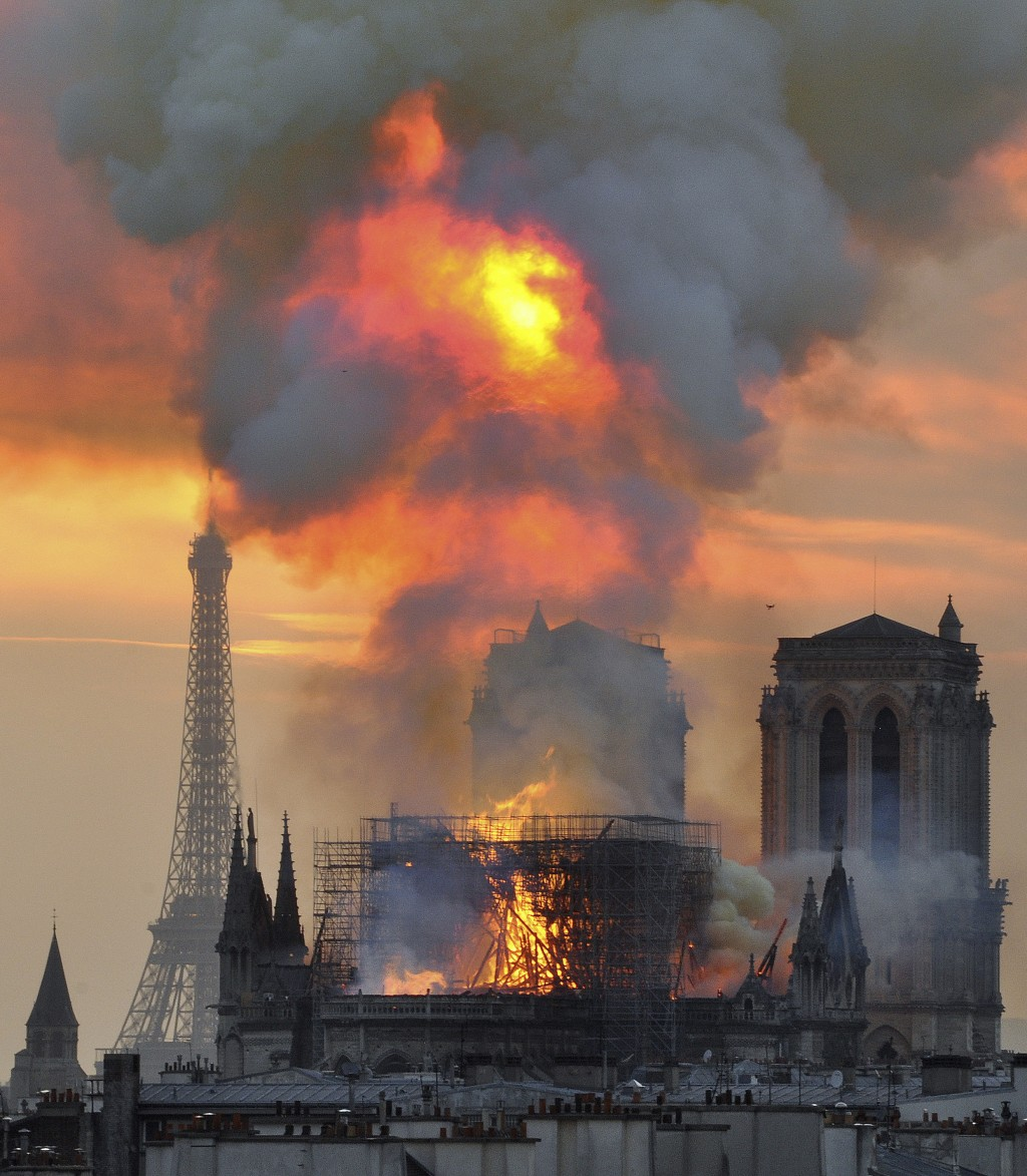 In this image made available on Tuesday April 16, 2019 flames and smoke rise from the blaze at Notre Dame cathedral in Paris, Monday, April 15, 2019. ...