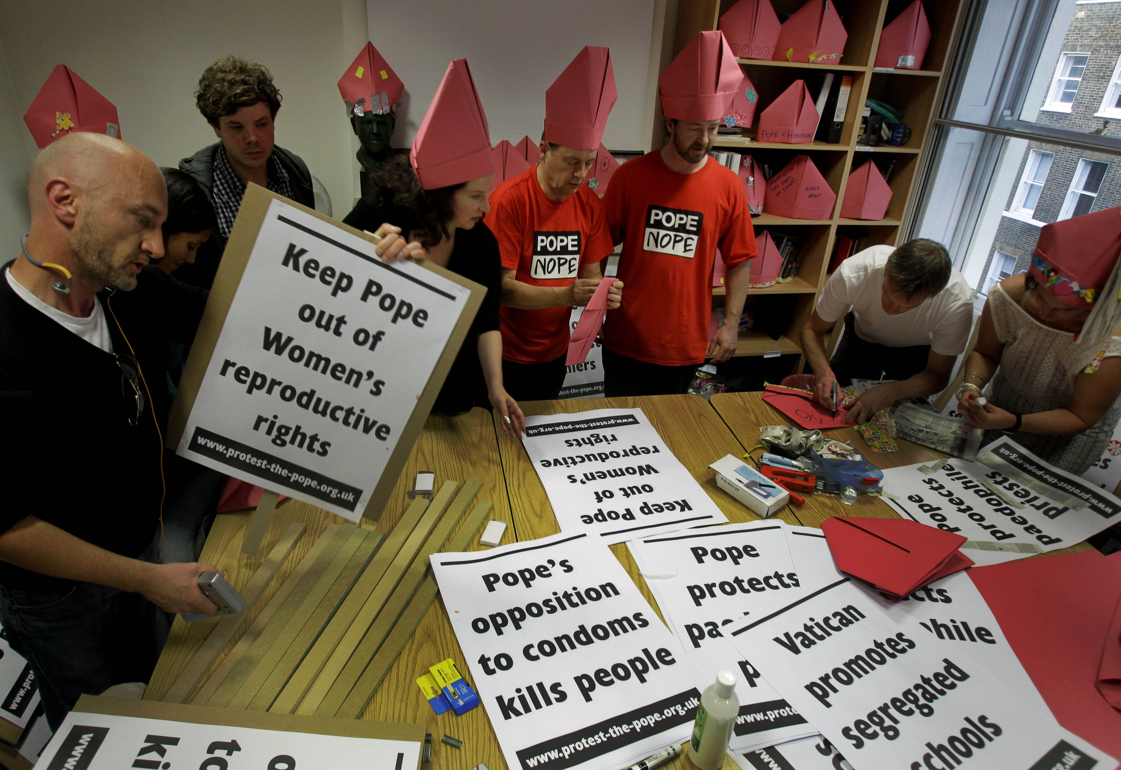 Members of the Protest the Pope campaign make placards in London on Wednesday for use at the march against the Pope's visit to the UK on Sep. 16.