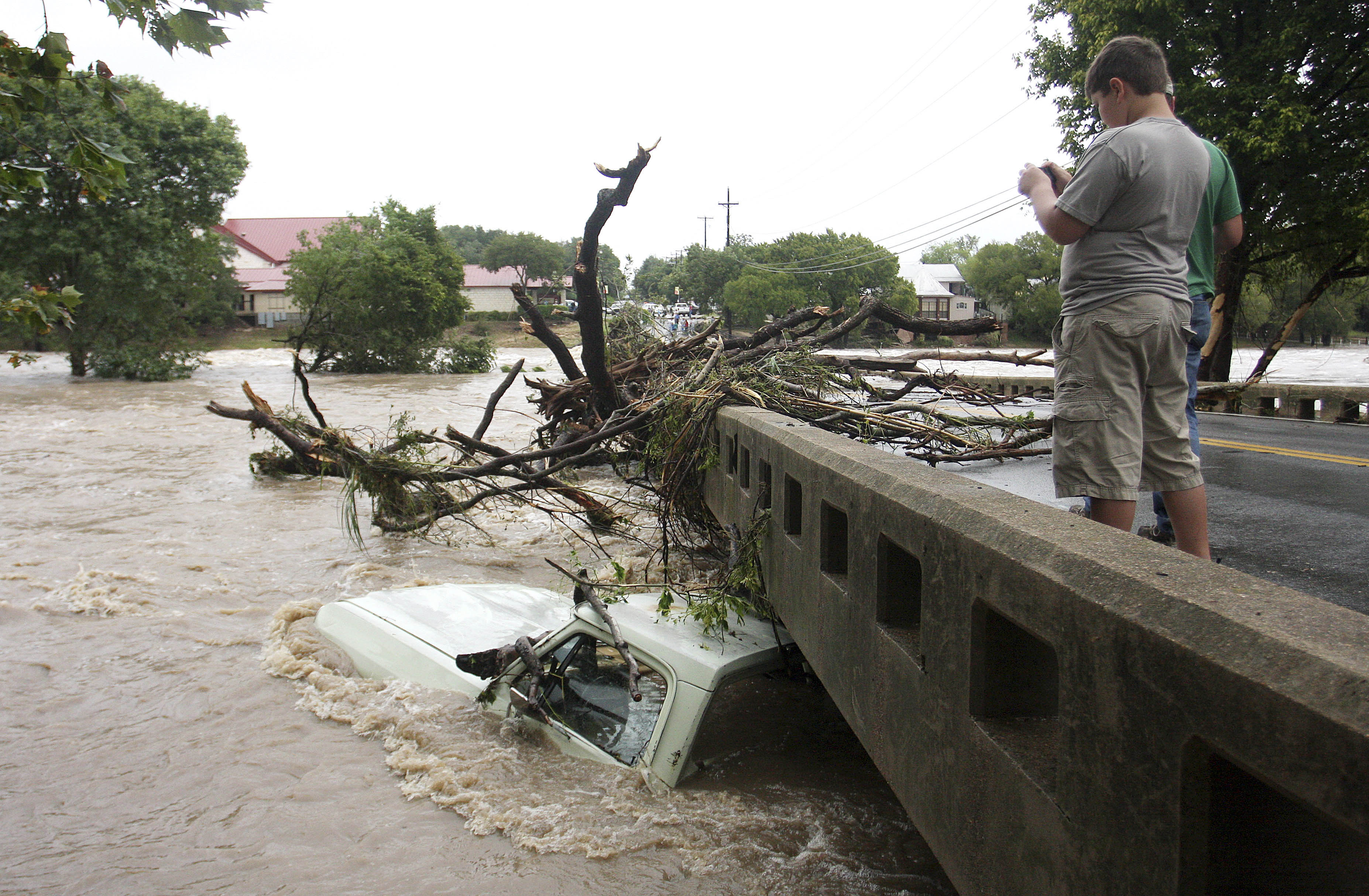 Visitors of Salado snap photos of a submerged truck under the Main Street bridge on Wednesday as the water began to recede, in Salado, Texas.