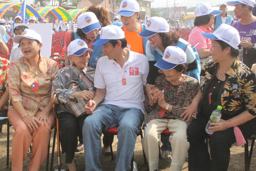總統馬英九(前中)5日在台中致贈「國旗福卡」平安符給9位逾8旬的長者,阿嬤們在合照前熱情地握著總統的手不放。總統也一直戴著阿嬤們為他祈來的...
