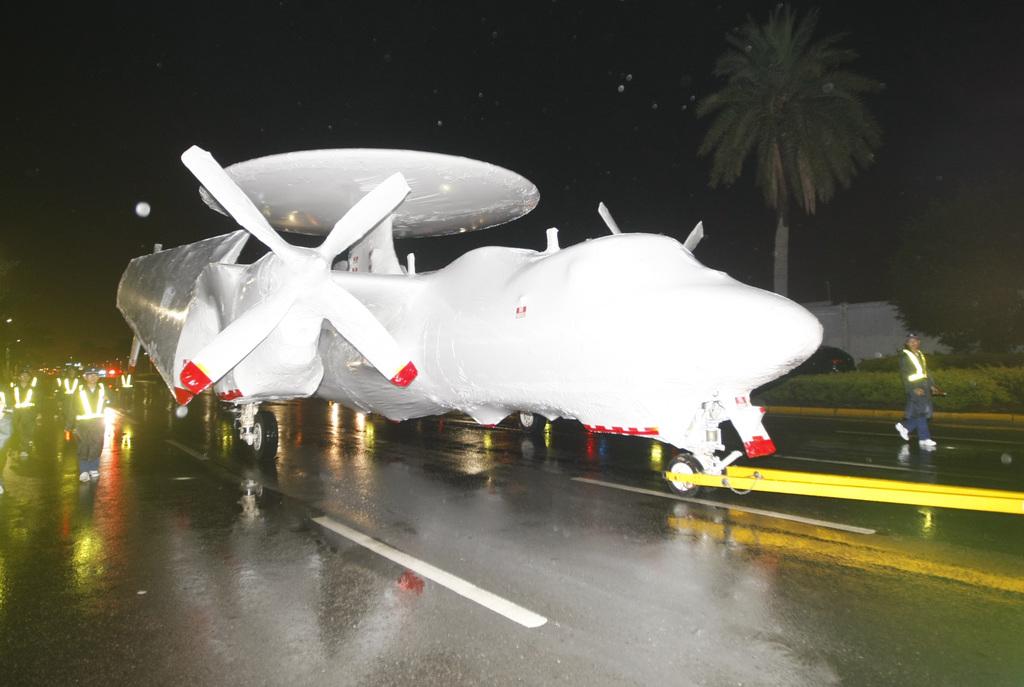 空軍兩架E-2T空中預警機8日凌晨從高雄小港機場以拖車運送到高雄港碼頭,並以白色不透明塑膠布,將整個機身包覆「變裝」,由海運裝載前往美國進...
