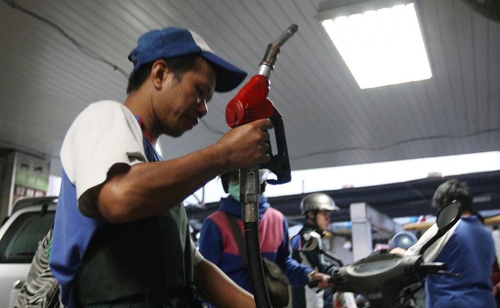 (檔案照片)台灣中油公司13日宣布,14日0時起,國內汽、柴油價格各減半調漲新台幣0.4元、0.5元,加油站員工忙得不可開交。中央社記者徐...