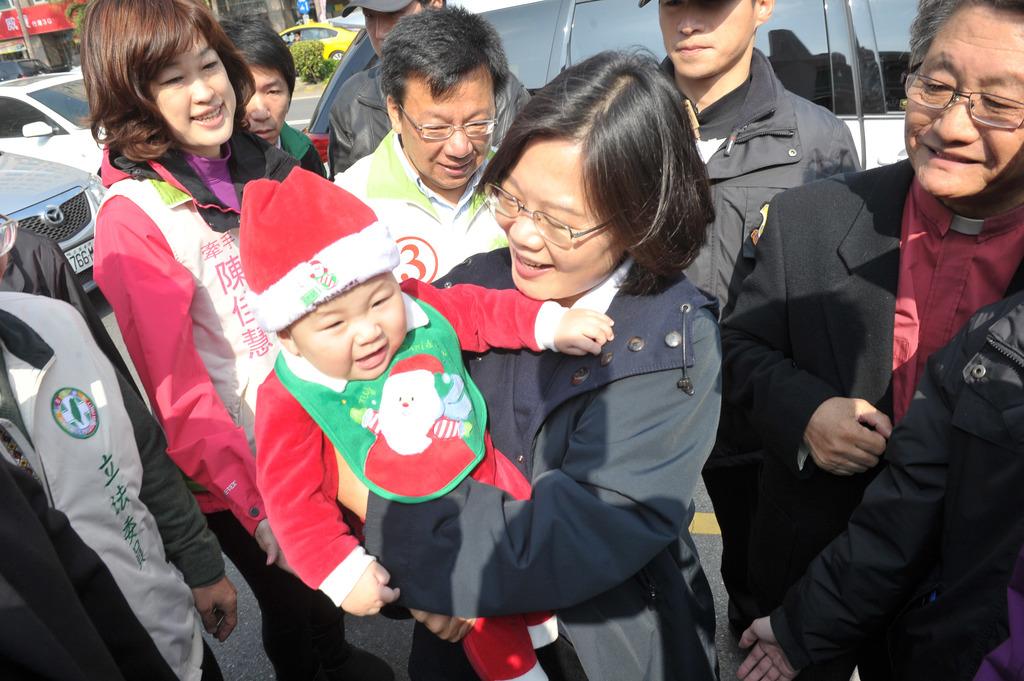 民進黨總統候選人蔡英文(中)24日在嘉義市,出席西門教會活動,到場時與熱情的教友握手致意,並抱起1名小孩。中央社記者施宗暉攝       ...