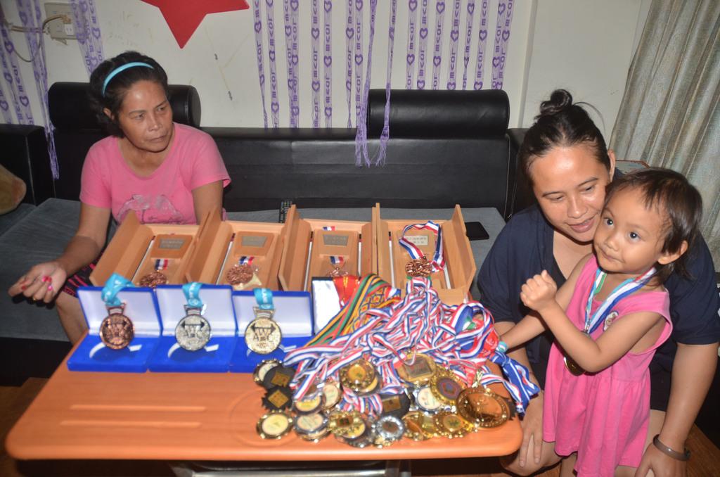 來自後山、阿美族單親家庭的舉重女孩郭婞淳,獲得獎牌超過50面,只缺奧運獎牌即能大滿貫。她的母親 (右2)和阿嬤 (左),23日拿出50多面...