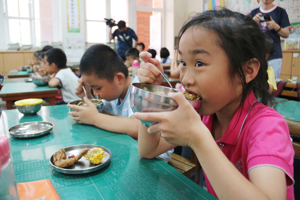 A girl eats a school lunch with fried chicken wings, vegetables, seaweed and tofu in Miaoli County,