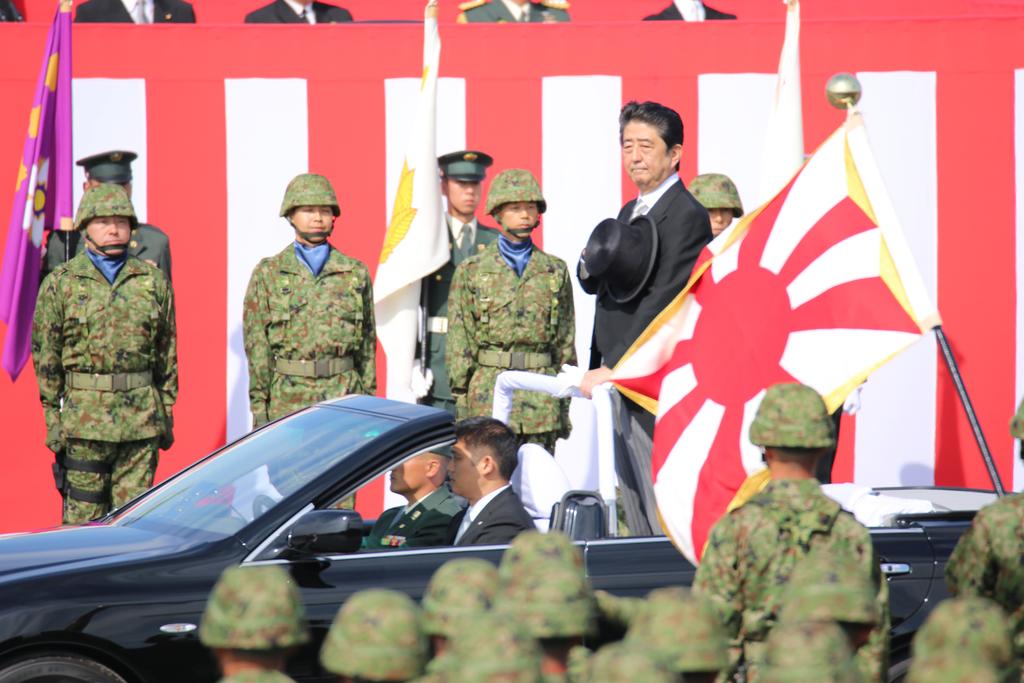 日本首相安倍晉三23日出席位於埼玉縣的自衛隊朝霞訓 練場舉行的觀閱儀式。他訓示說,自衛隊員將被賦予新 任務,為了守護尊貴的和平,將此交給下
