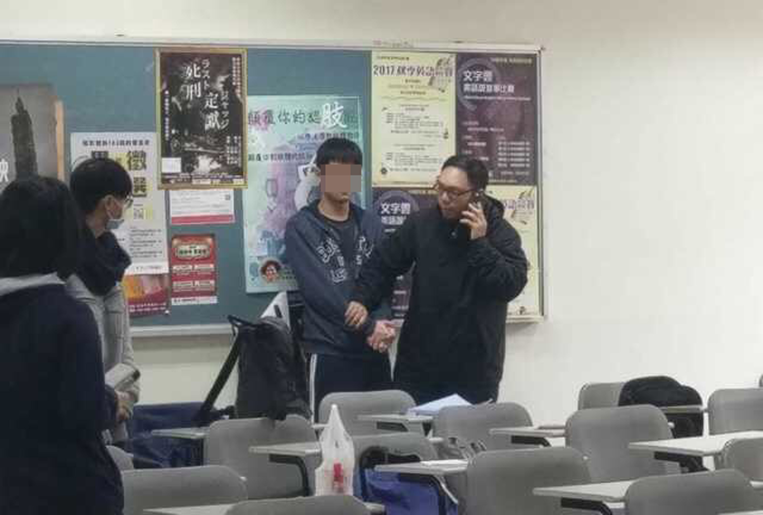 Chen being restrained by teachers after assault.
