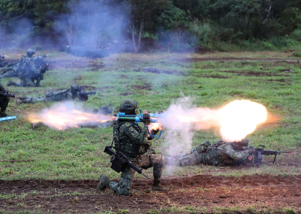 Soldier fires shoulder-mounted rocket during drill.