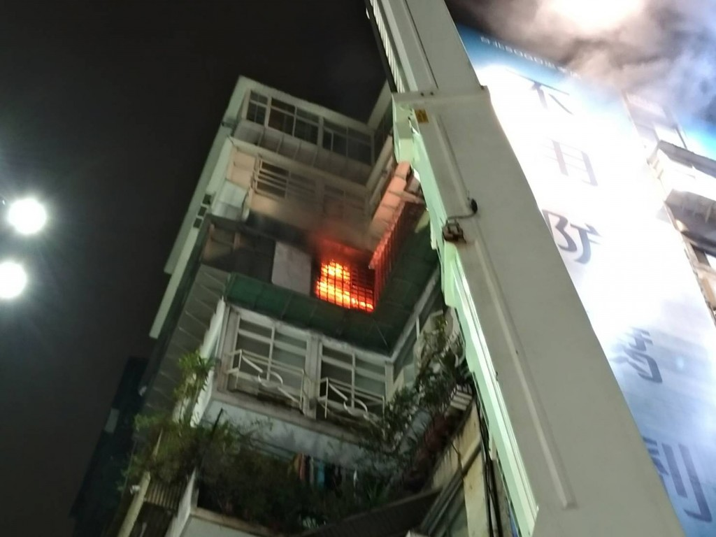 台北市忠孝東路知名百貨旁大樓傳出火警,派出消防人 員趕赴現場,屋內橘色火光清晰可見,並飄出陣陣白煙 ,目前持續搶救中。 (民眾提供)