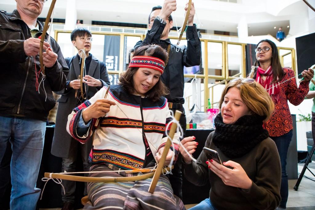 編織藝術家陳秀玉(中)當地時間11日在大英圖書館,示範泰雅族傳統弓織技藝,吸引許多民眾參與。(駐英處文化組提供)