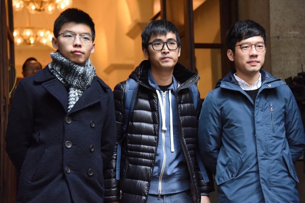 黃之鋒(左)、羅冠聰(右)及周永康(中)先前在香港法院前合影畫面。