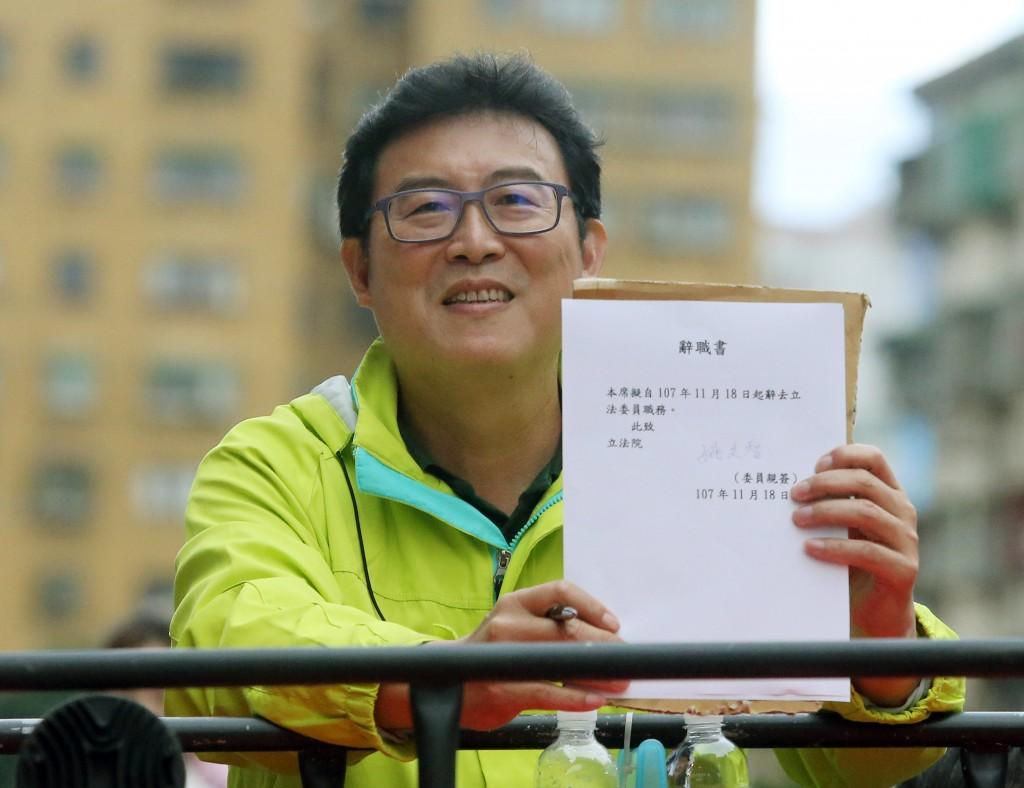 民進黨台北市長候選人姚文智19日下午進行車隊掃街, 途中車隊暫停,姚文智在競選車上簽署立法委員辭職書 並向民眾展示。 中央社記者郭日