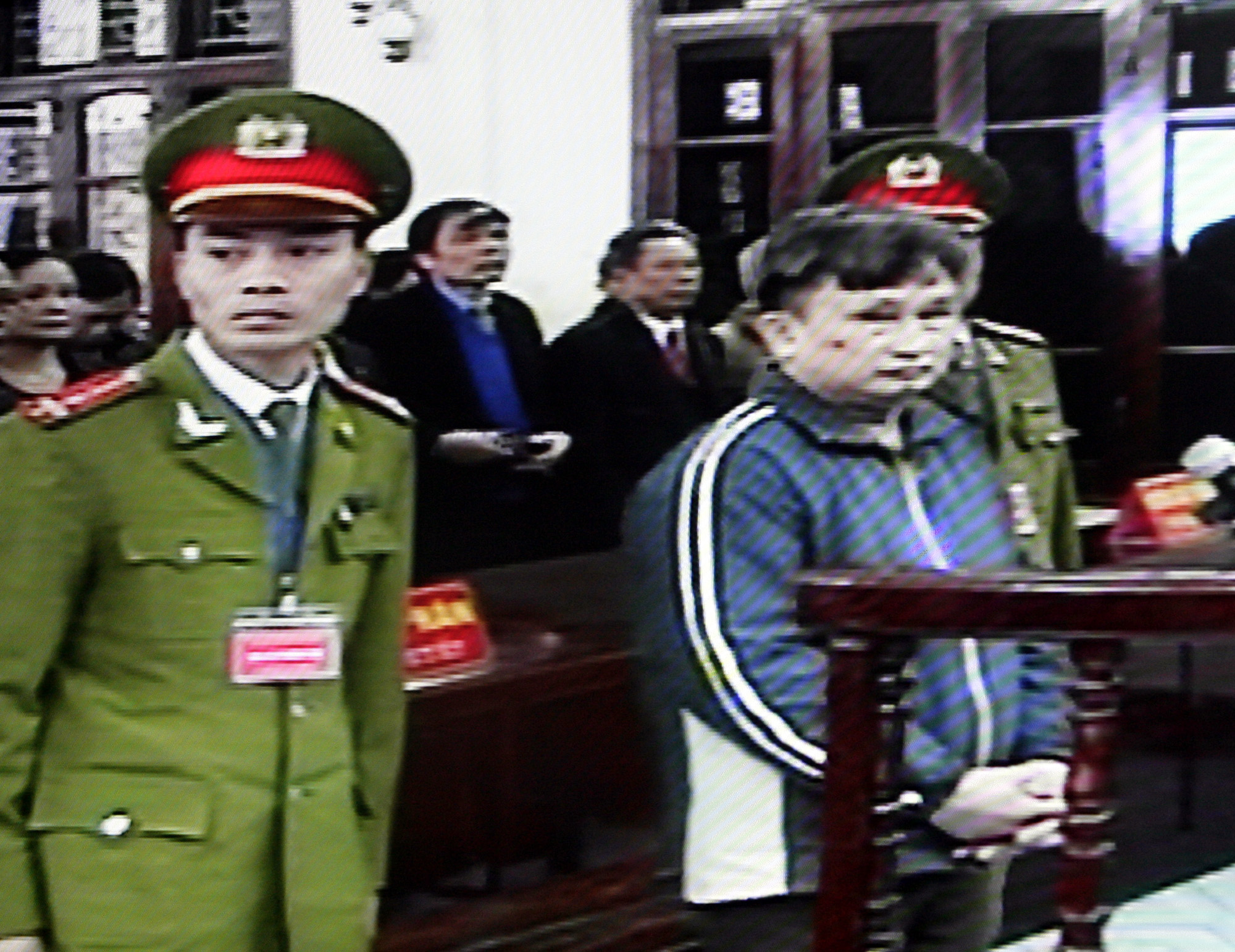 In this photo taken from a closed-circuit television at the courthouse, Tran Anh Kim, center, appears at his trial in Thai Binh province, Vietnam yest...
