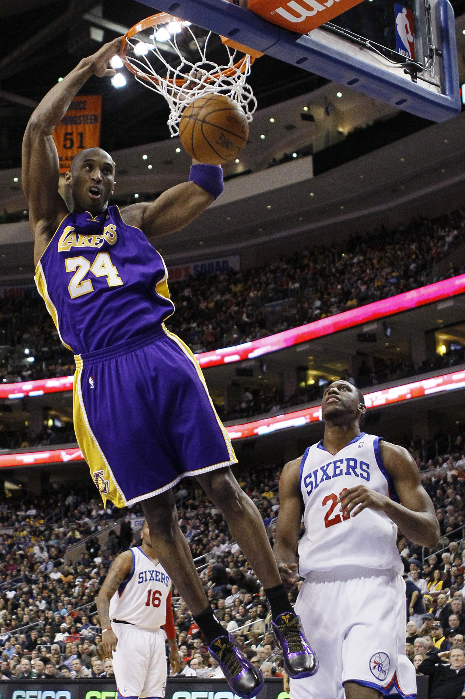 Lakers' Kobe Bryant, left, dunks as Philadelphia 76ers' Thaddeus Young looks on in the first half of an NBA basketball game on Friday in Philadelphia,...