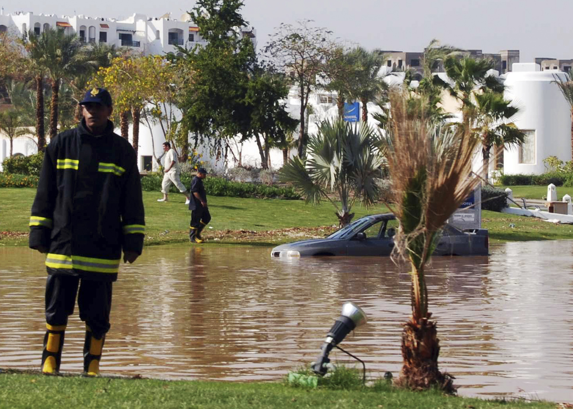 Egyptians rescuers are seen next to a car stuck in floodwater, at the Red Sea resort of Sharm el-Sheik, Egypt on Jan. 19. Heavy rains and flash floods...