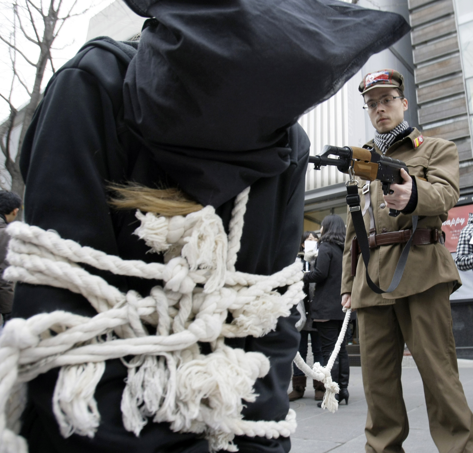 A human rights activist Olivier Courapied of France, wearing North Korean soldier's uniform, aims a mock North Korean asylum-seeker tied up with ropes...