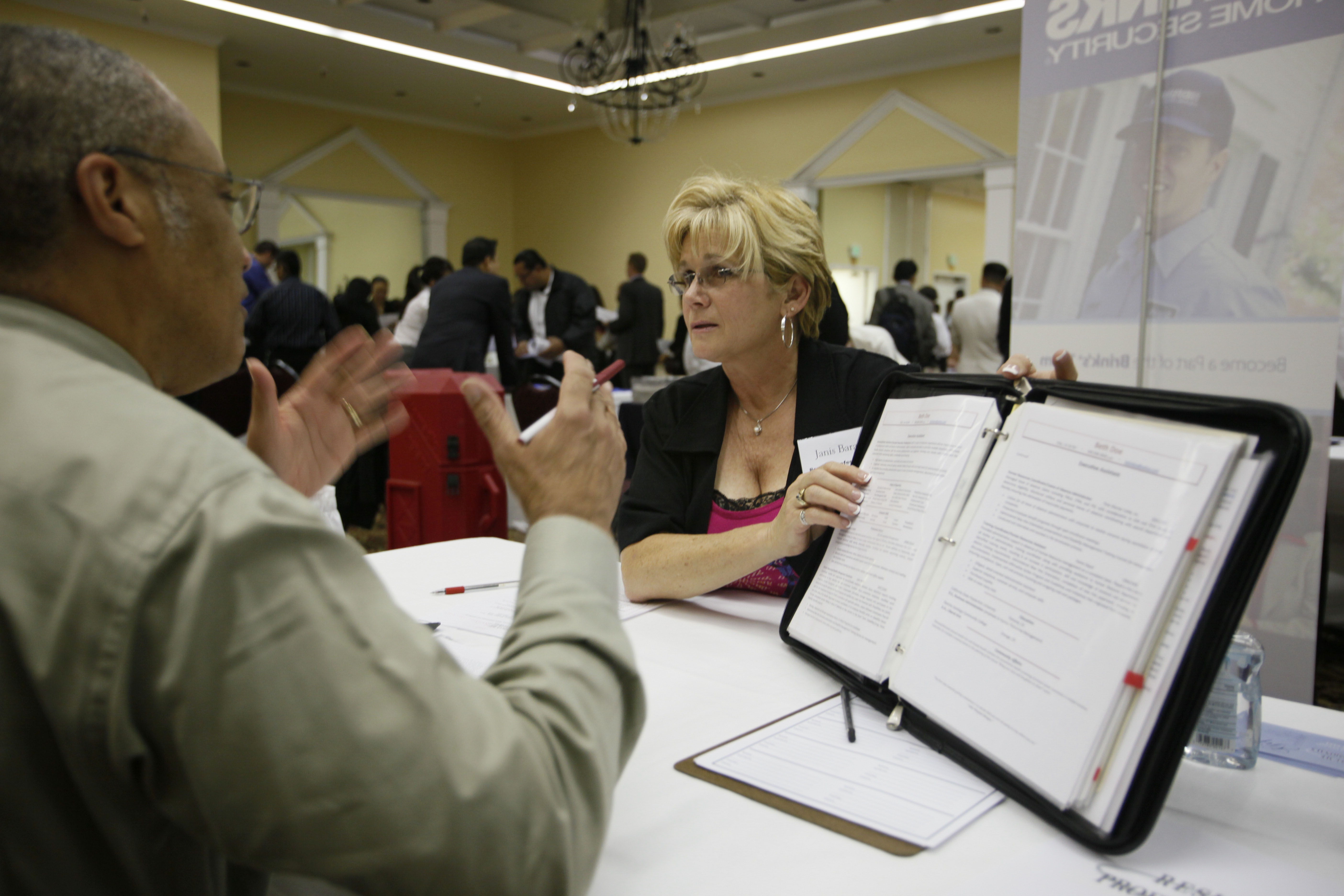 Stafford Muller, left, of Fremont, California, gets help with his resume from Janis Barat, right, of Resume Professionals at a career fair put on by N...