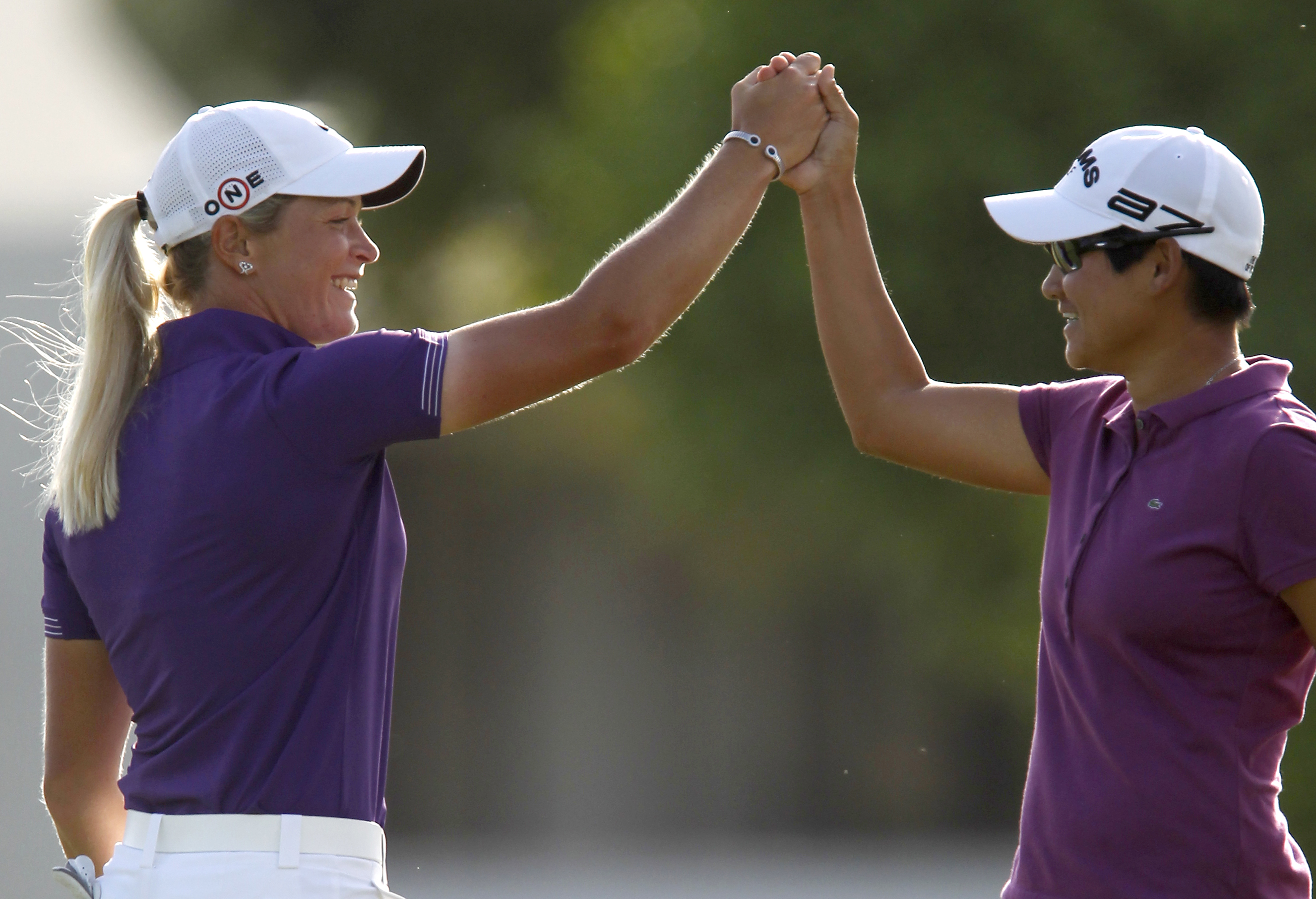 Suzann Pettersen, of Norway, and Yani Tseng, of Taiwan, celebrate a pair of birdies on the 18th hole during the third round of the LPGA Kraft Nabisco ...