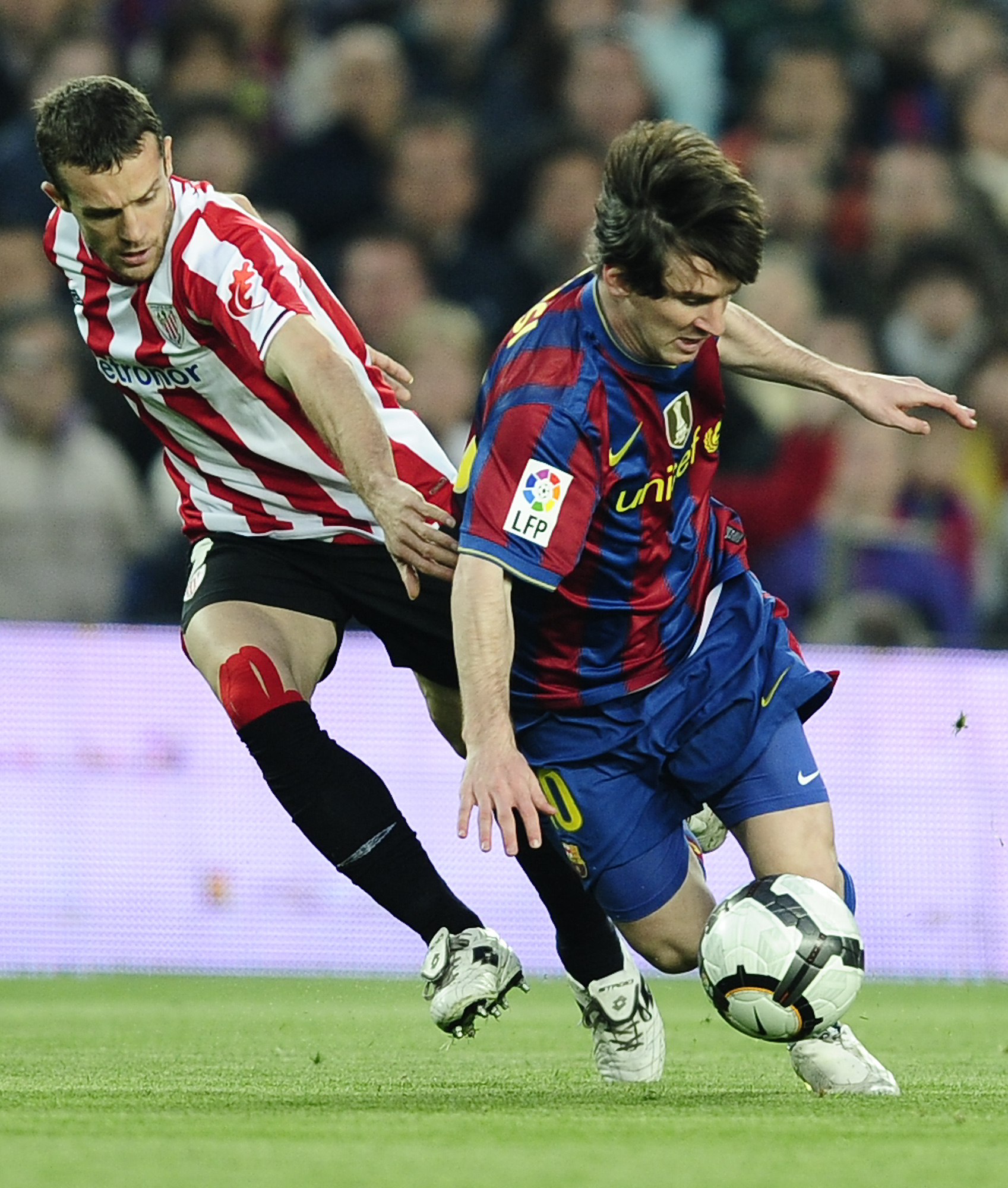 FC Barcelona's Lionel Messi from Argentina, right, duels for the ball against Athletic Bilbao's Koikili Lertxundi during their Spanish La Liga soccer ...