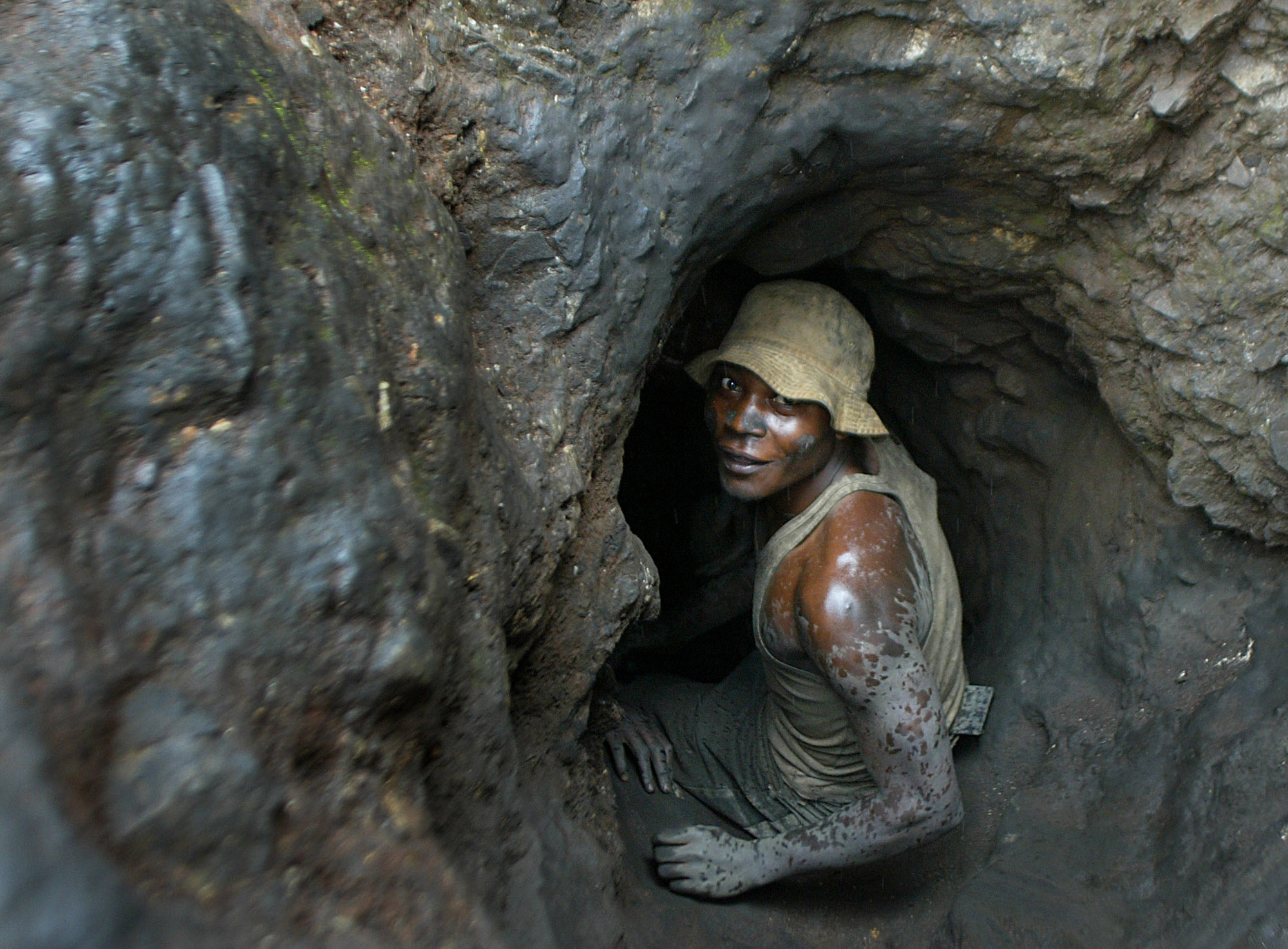 In this April 2004 file photo, a man enters a tunnel dug with shovels in the Shinkolobwe cobalt mine, 35km (22 miles) from the town of Likasi in the D...