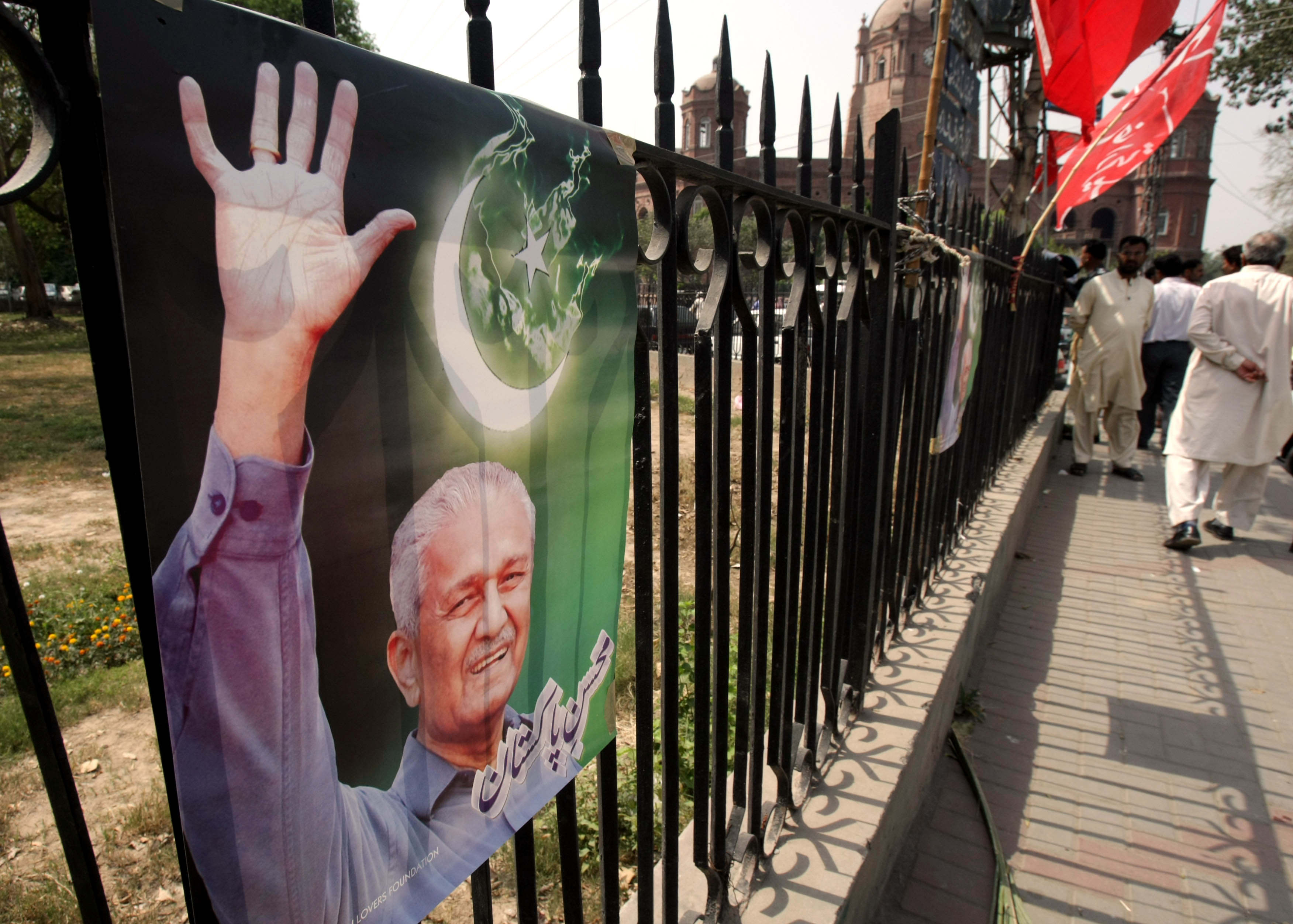 A poster on a fence in Lahore, Pakistan shows Pakistani nuclear scientist A.Q. Khan, glorified by many of his countrymen but reviled by Western govern...