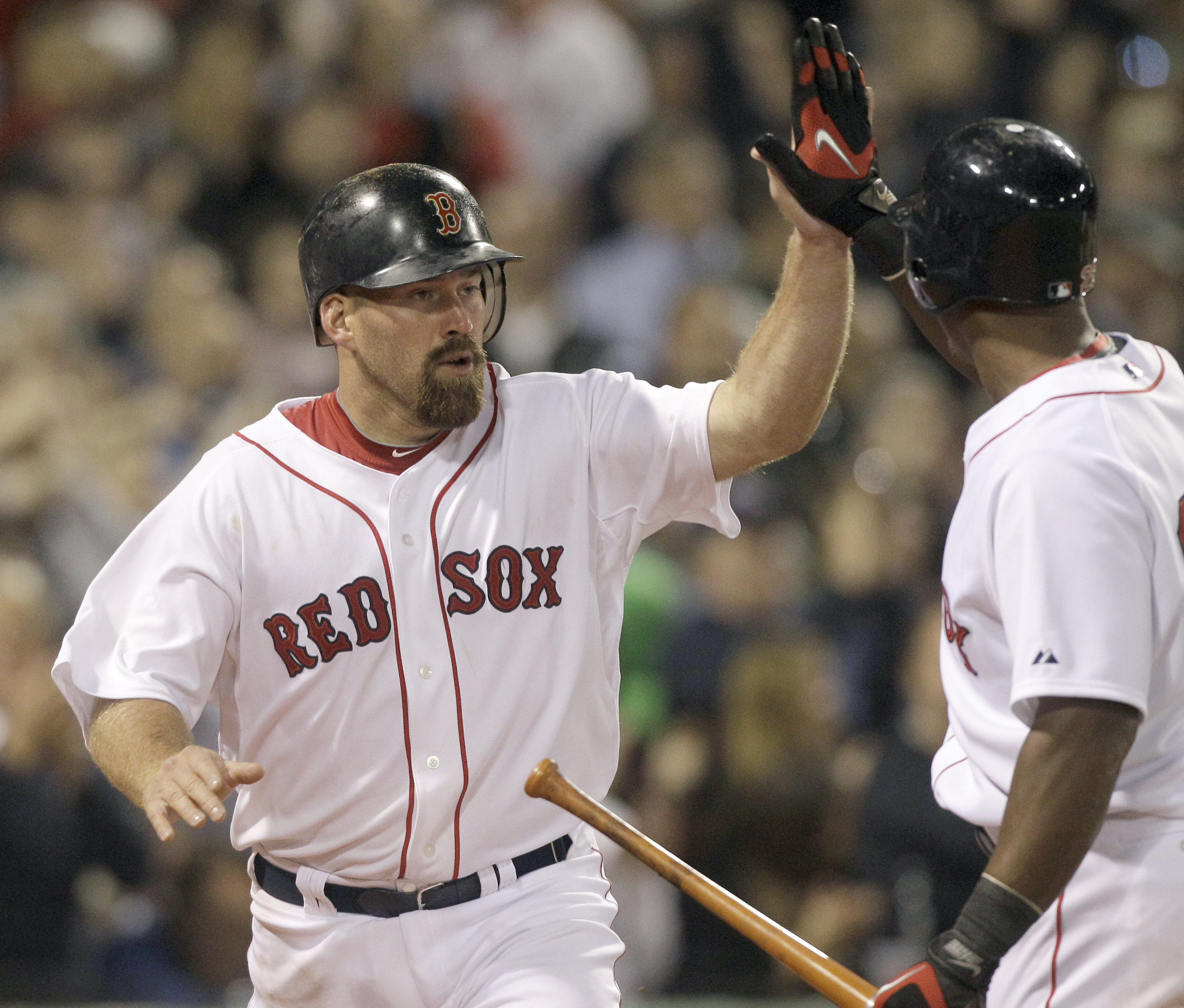 Boston Red Sox's Kevin Youkilis, left, is congratulated by Adrian Beltre after scoring on a passed ball in the seventh inning against the New York Yan...