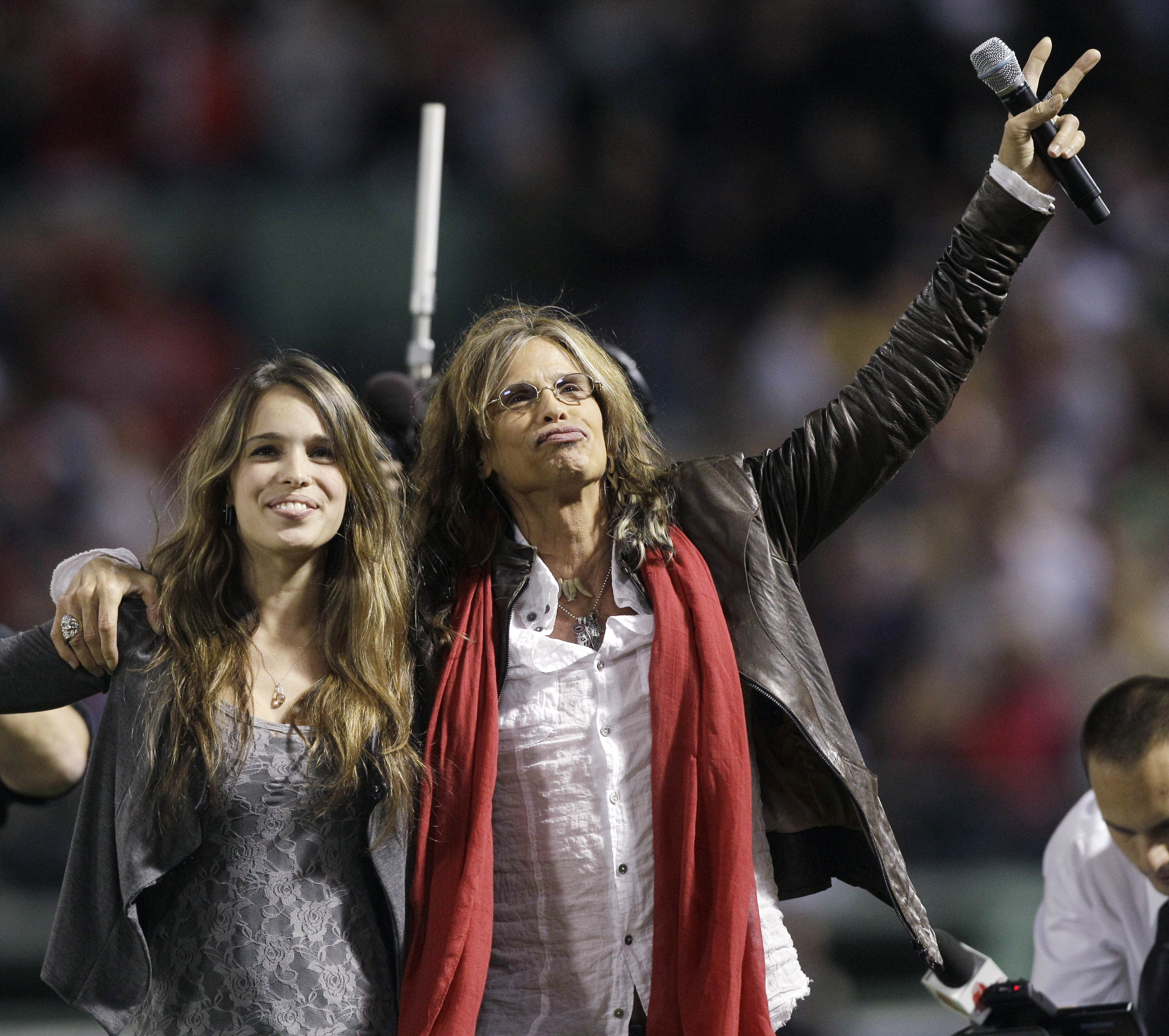 4. Aerosmith's Steven Tyler, with daughter Chelsea, left, waves after singing 'God Bless America' during the seventh-inning stretch of the opening gam...