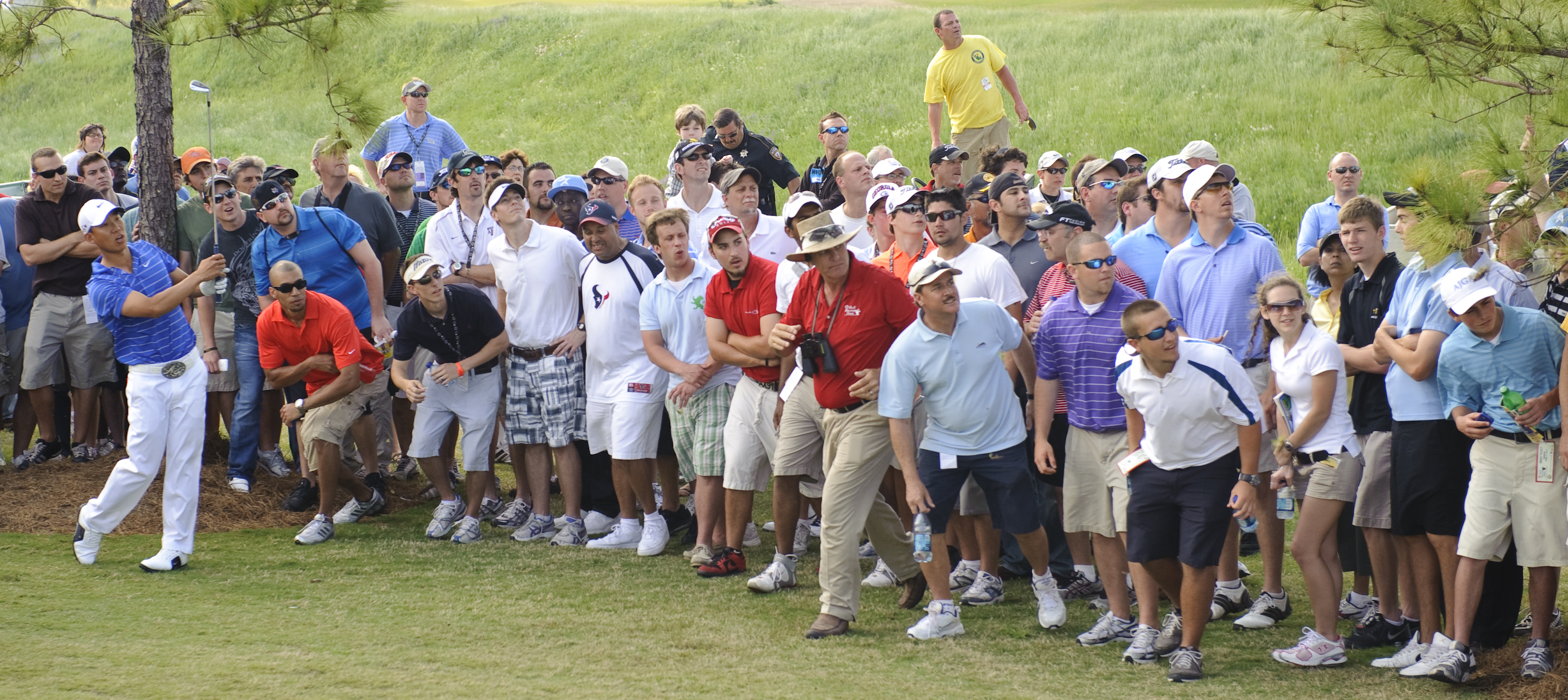 Anthony Kim watches his second shot on the 17th hole as the gallery crowds in to see it land on the green during the final round of the Houston Open P...