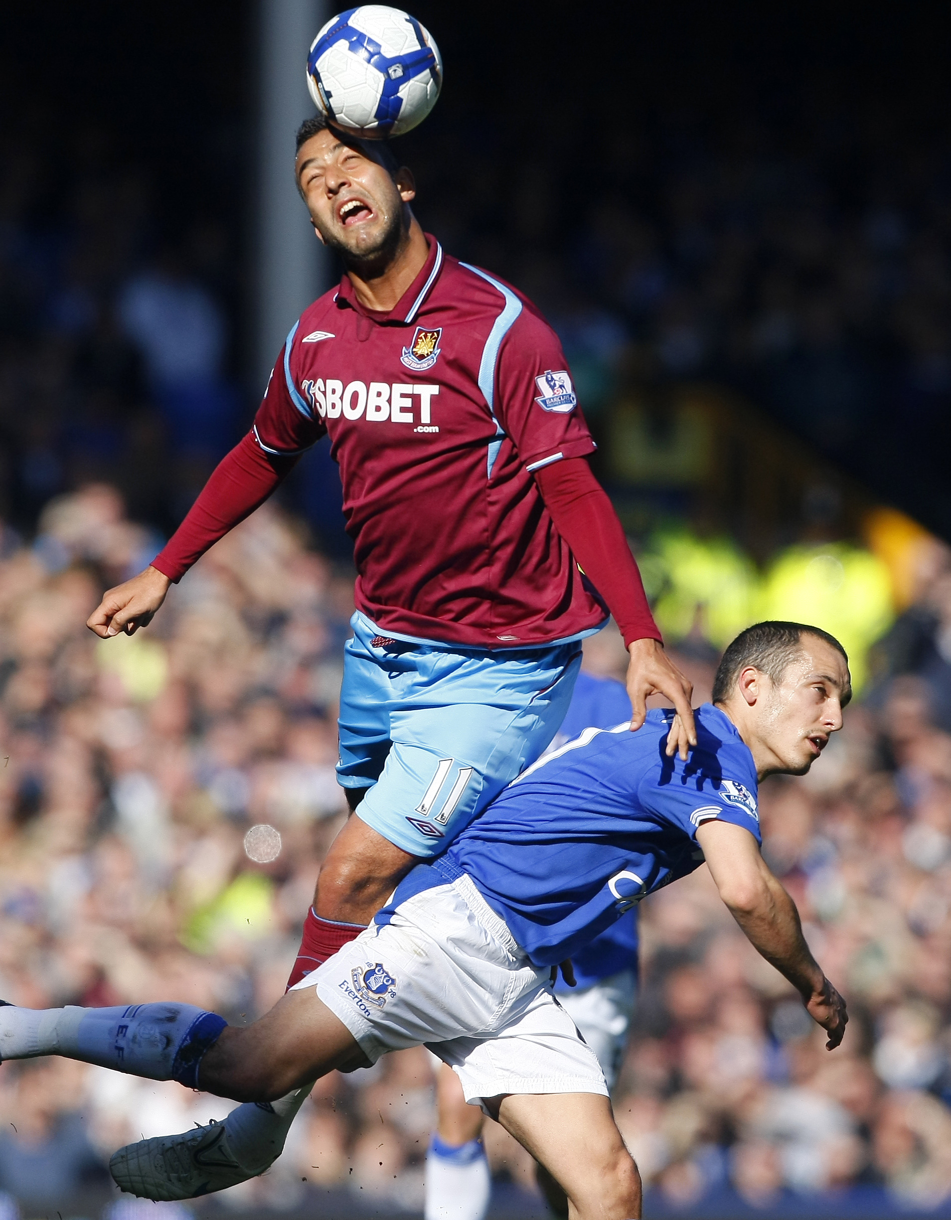 Everton's Tim Cahill, top, vies for the ball against West Ham's Carlton Cole during their English Premier League soccer match at Goodison Park, Liverp...