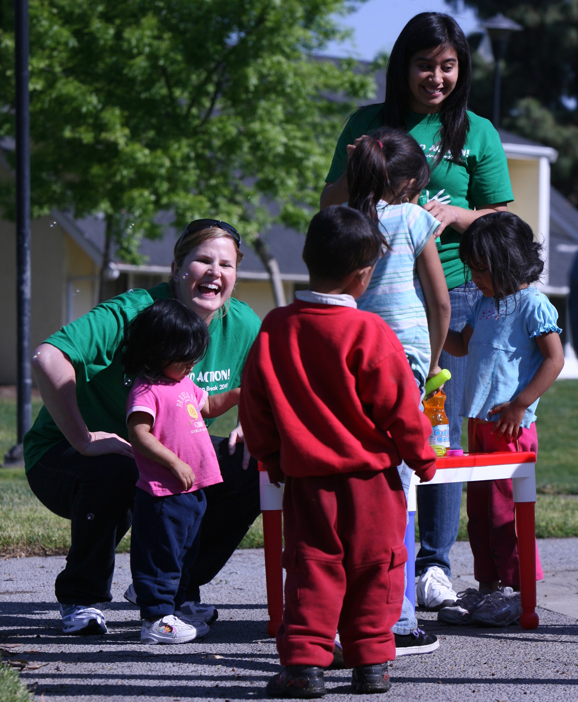 Fresno State students Alison Edwards, left, and Valeria Ramirez, right, teach kids to blow bubbles at Bigby Villa Apartments in Fresno, California on ...