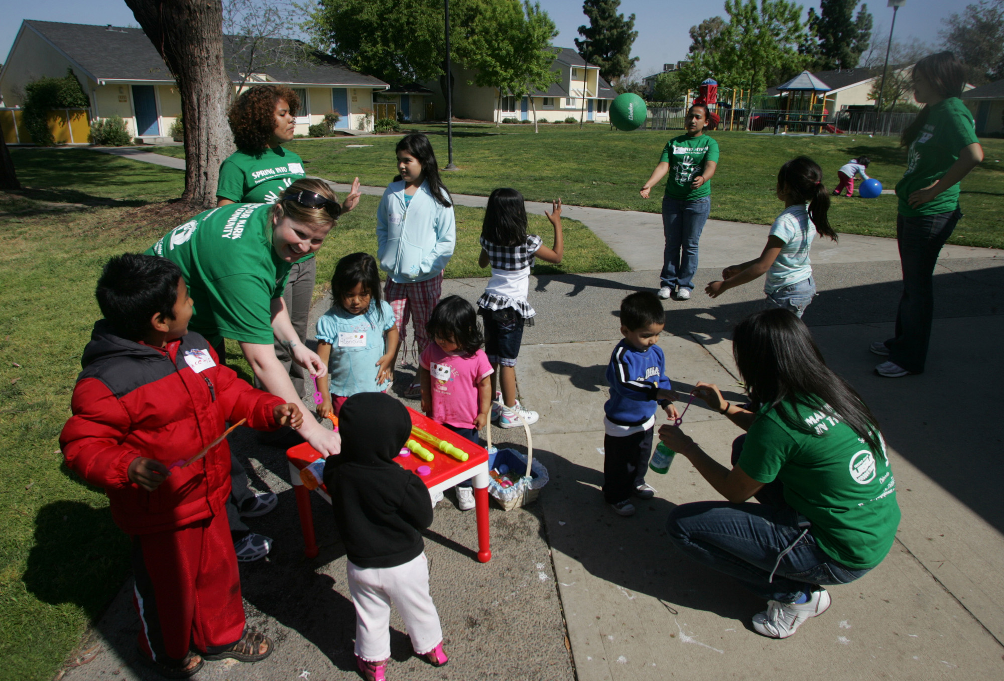 Fresno State students, green T-shirts, play with a group of children at Bigby Villa Apartments in Fresno, California on March 27.
