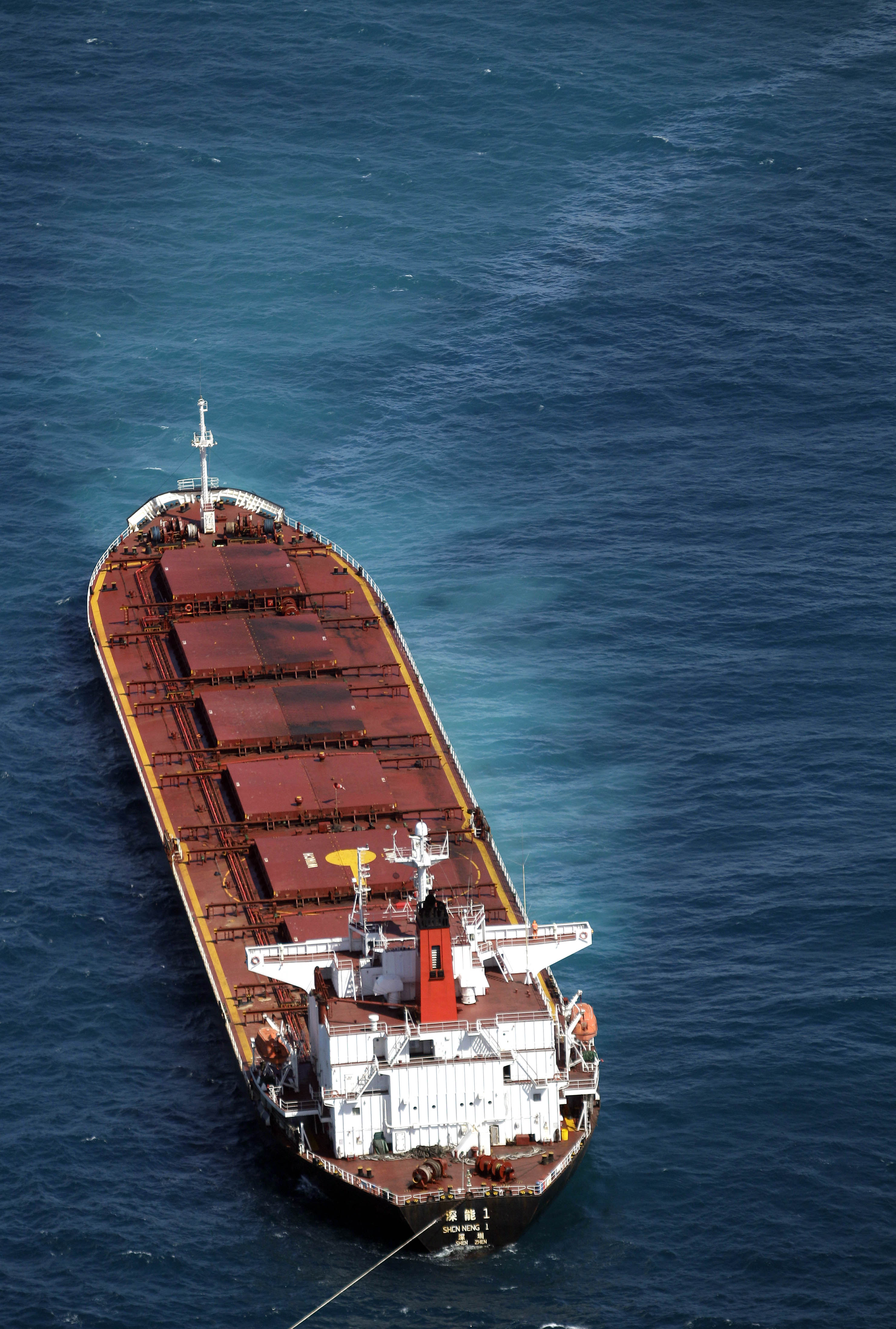 A ribbon of oil snakes away on the surface from the Chinese-registered 230m-long bulk coal carrier Shen Neng 1, off the coast of Rockhampton, Australi...