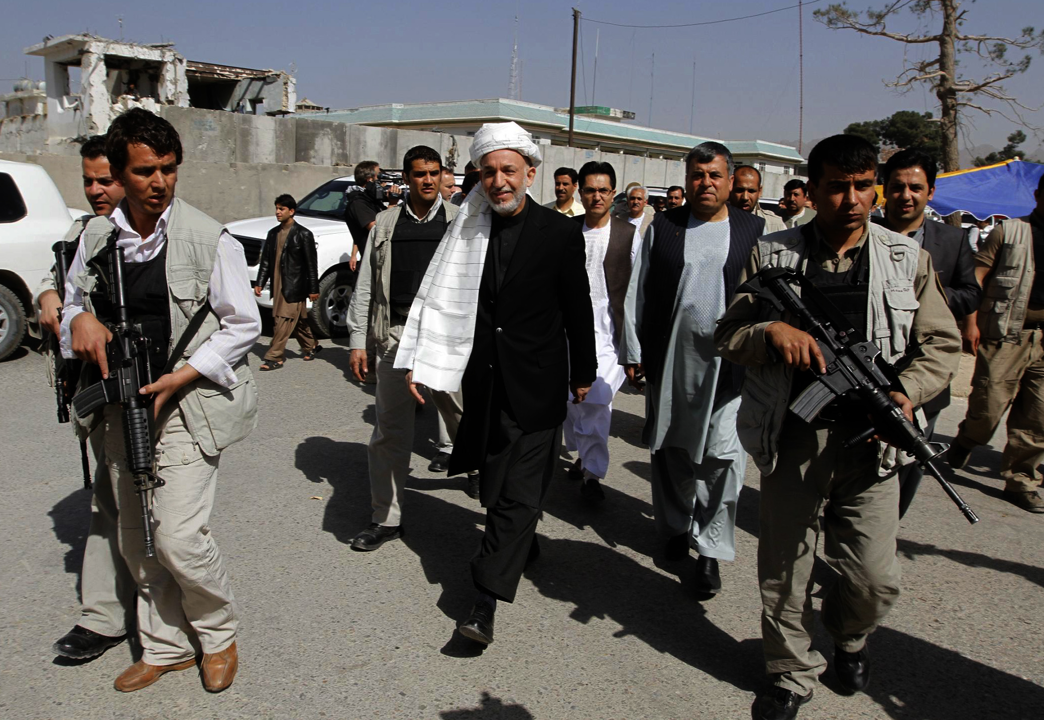 Afghan President Hamid Karzai, center, surrounded by his body guards walks through Kandahar city, south of Kabul, Afghanistan yesterday.