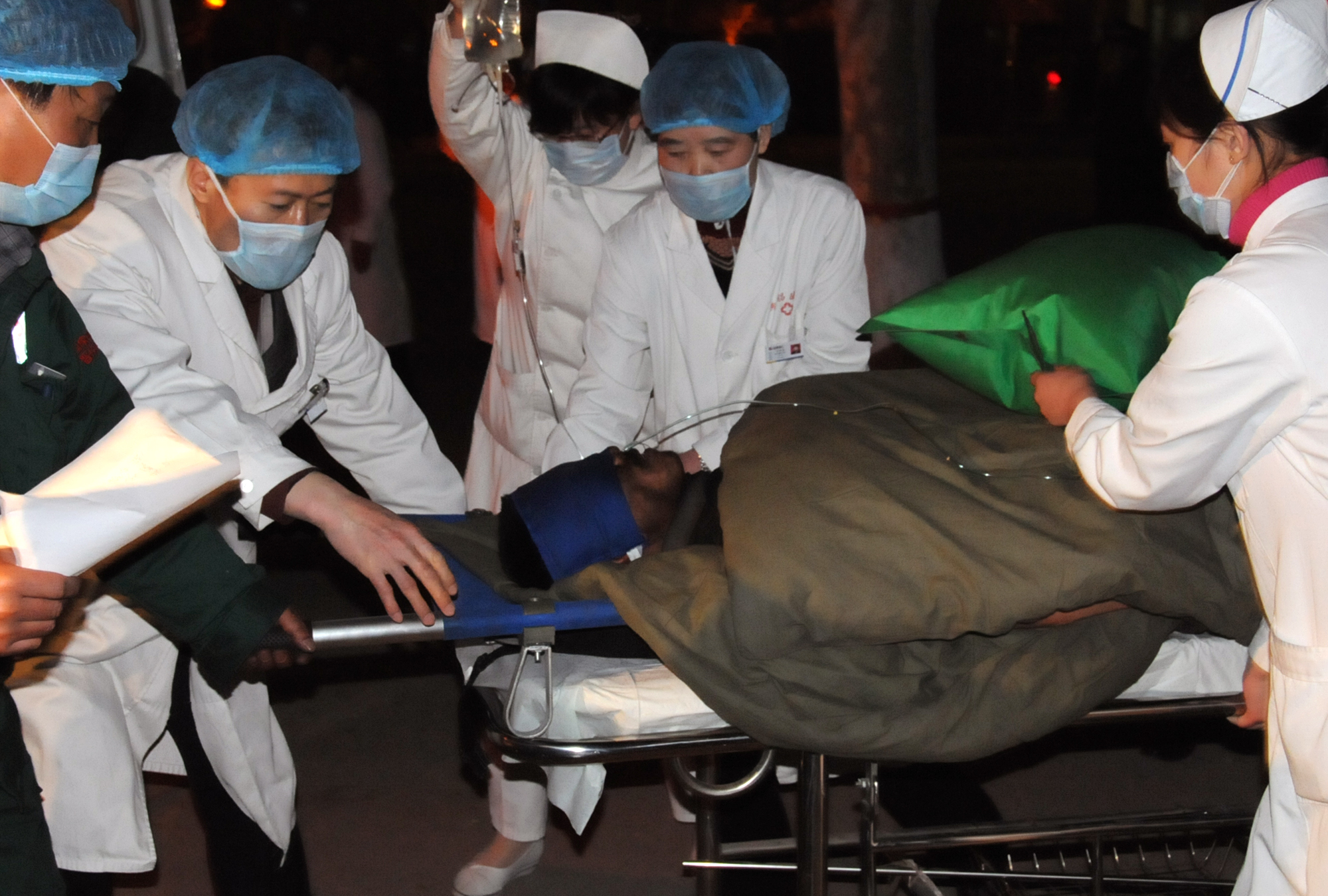 In this photo provided by China's Xinhua News Agency, a rescued miner is taken to a hospital in Xiangning County, north China's Shanxi Province yester...