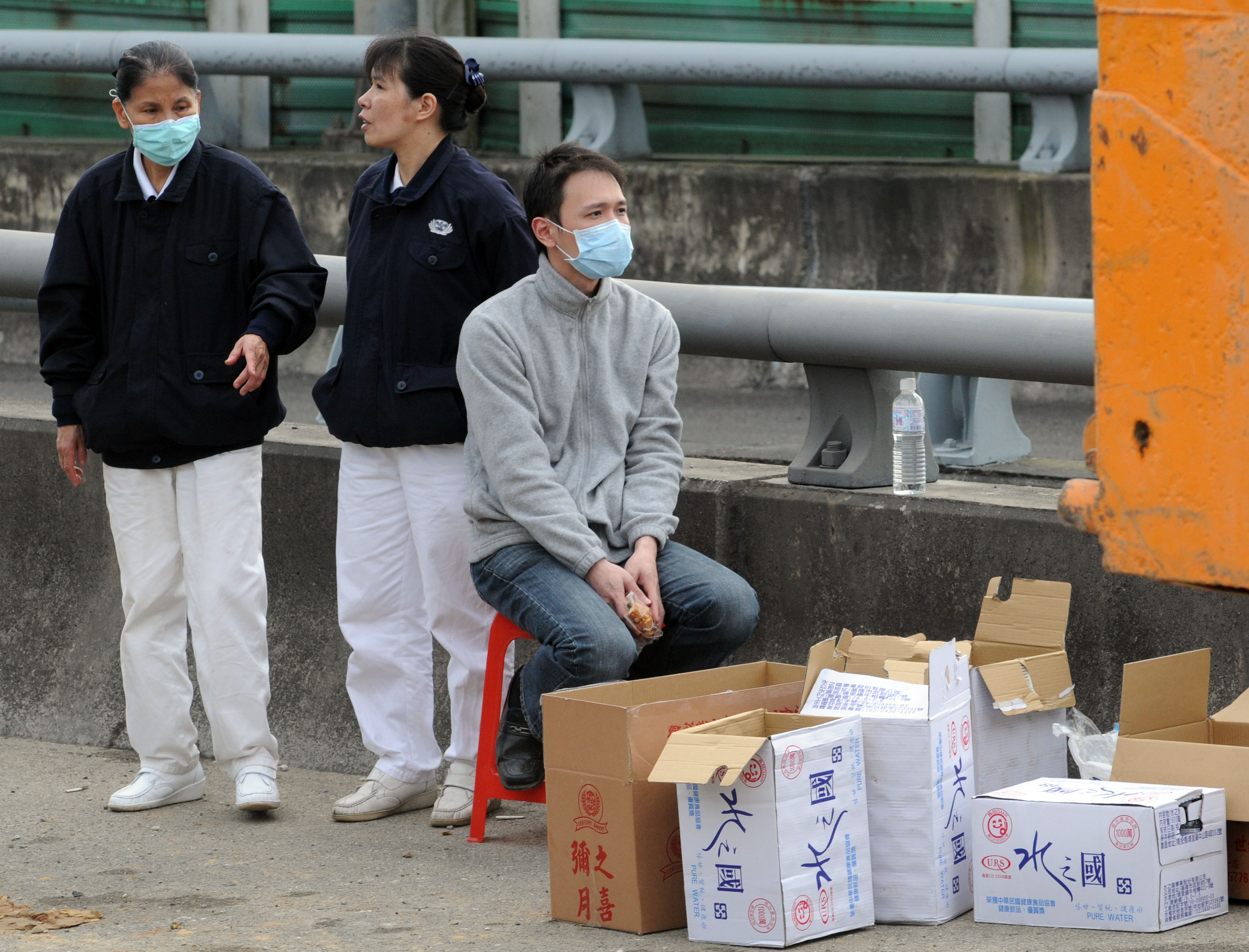 A young man, right, waits for news of the rescue operation on the No.3 Freeway yesterday in the company of volunteers from the Buddhist Compassion Rel...