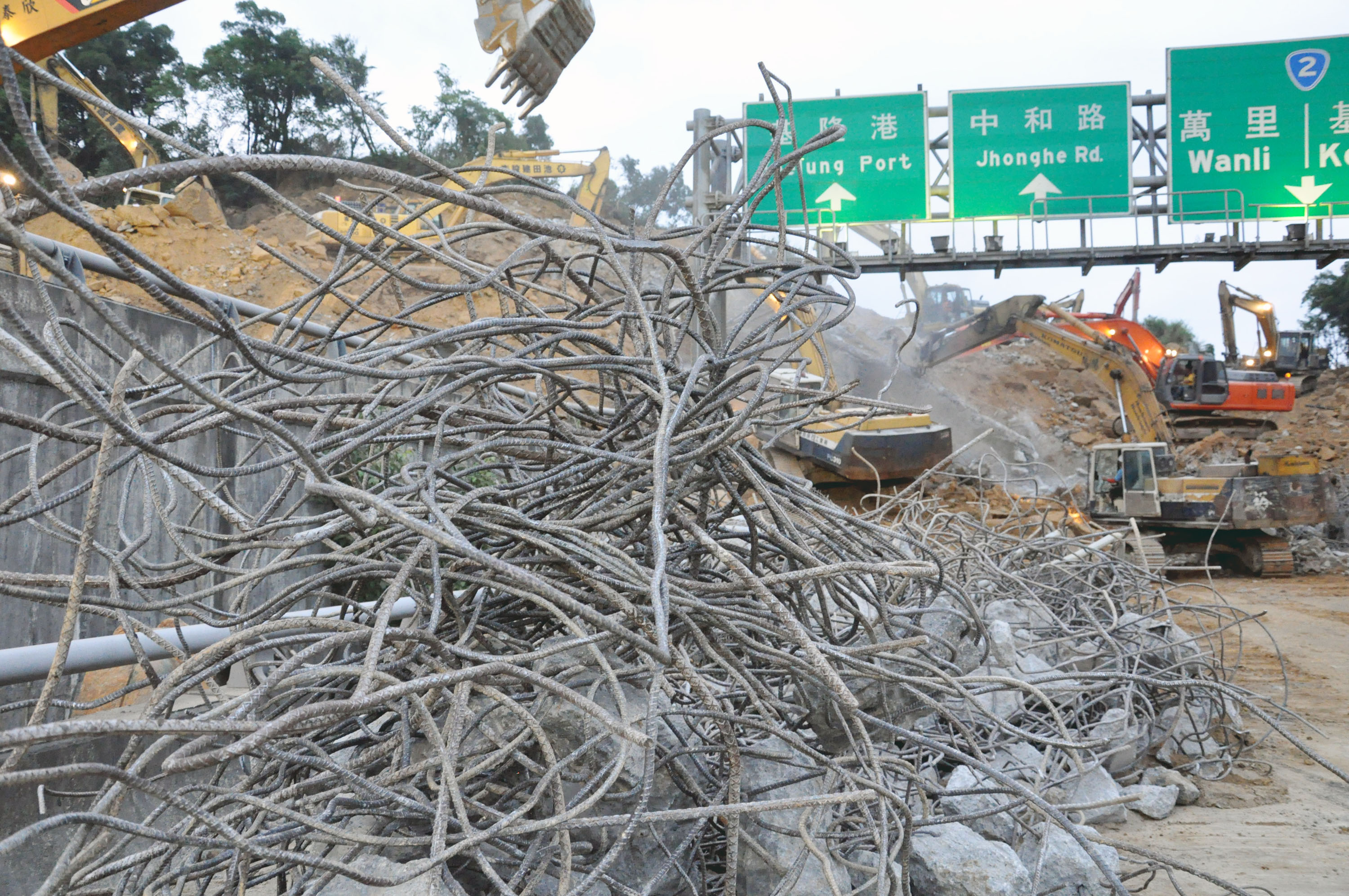 Excavators succeed in removing the steel cables from the overpass destroyed by the landslide on the No.3 Freeway near Keelung yesterday morning, but w...