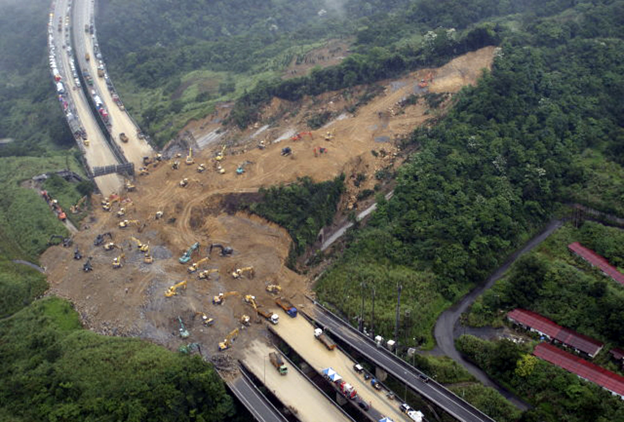 In this photo provided by Taiwan's National Airborne Service Corps, excavators dig in massive mud caused by landslide for missing people on a roadway ...