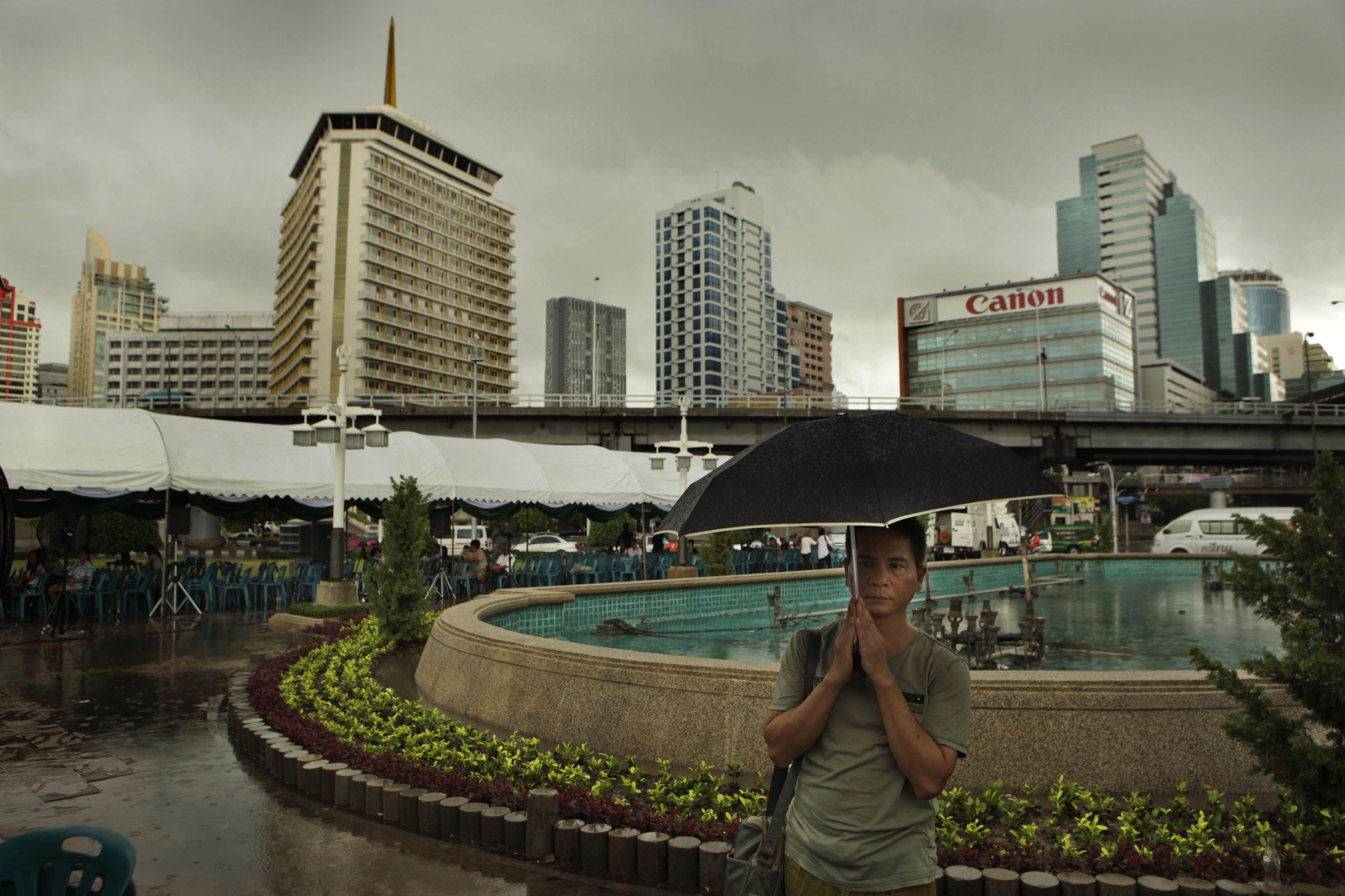 A Thai man prays in the rain during an all religion prayer meeting for peace and harmony at the Lumpini park, in downtown Bangkok, Thailand on Wednesd...