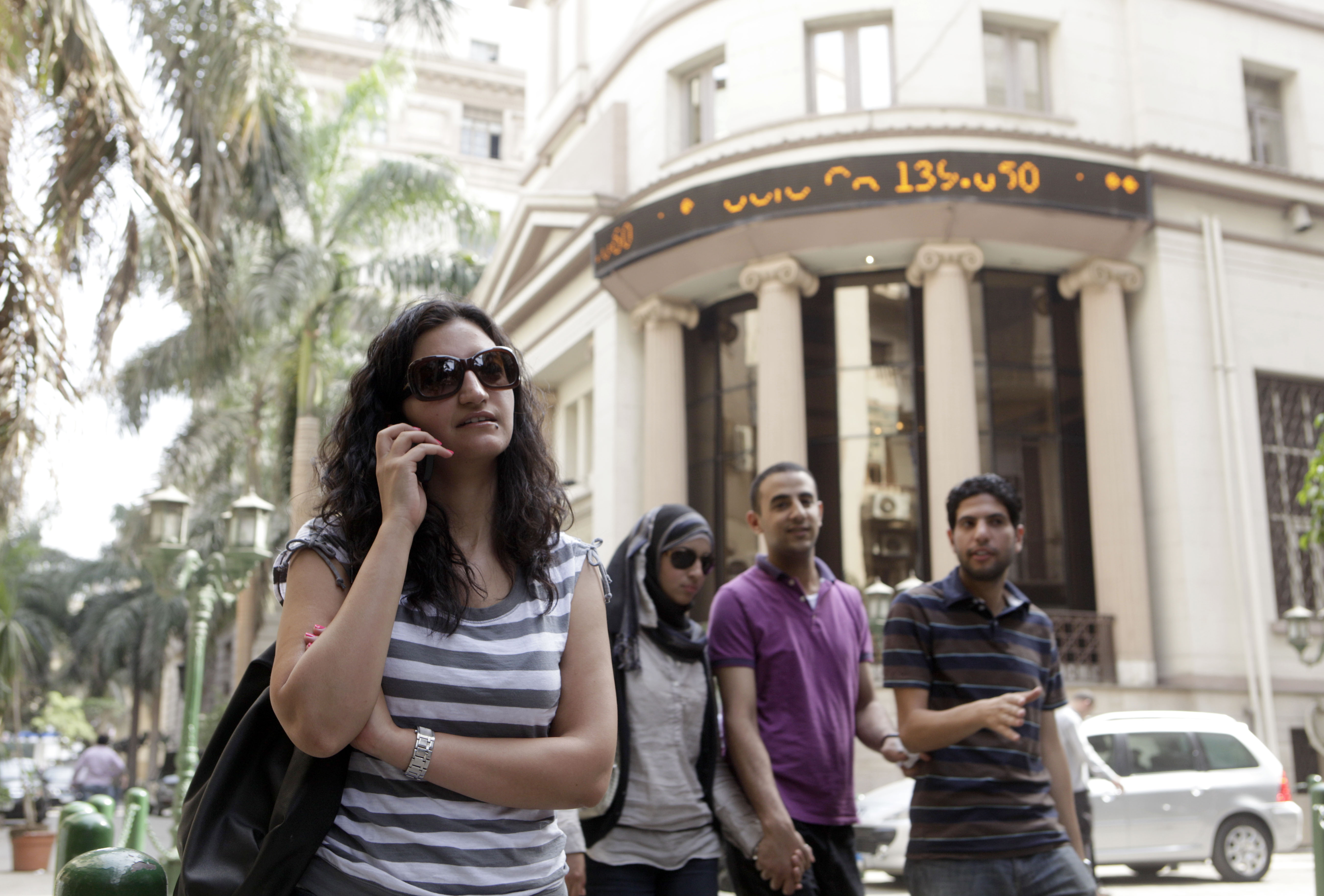 Noha al-Shahed, a 28-year-old stock trader, left, talks on her mobile in front of Cairo stock market in Egypt on May 20.